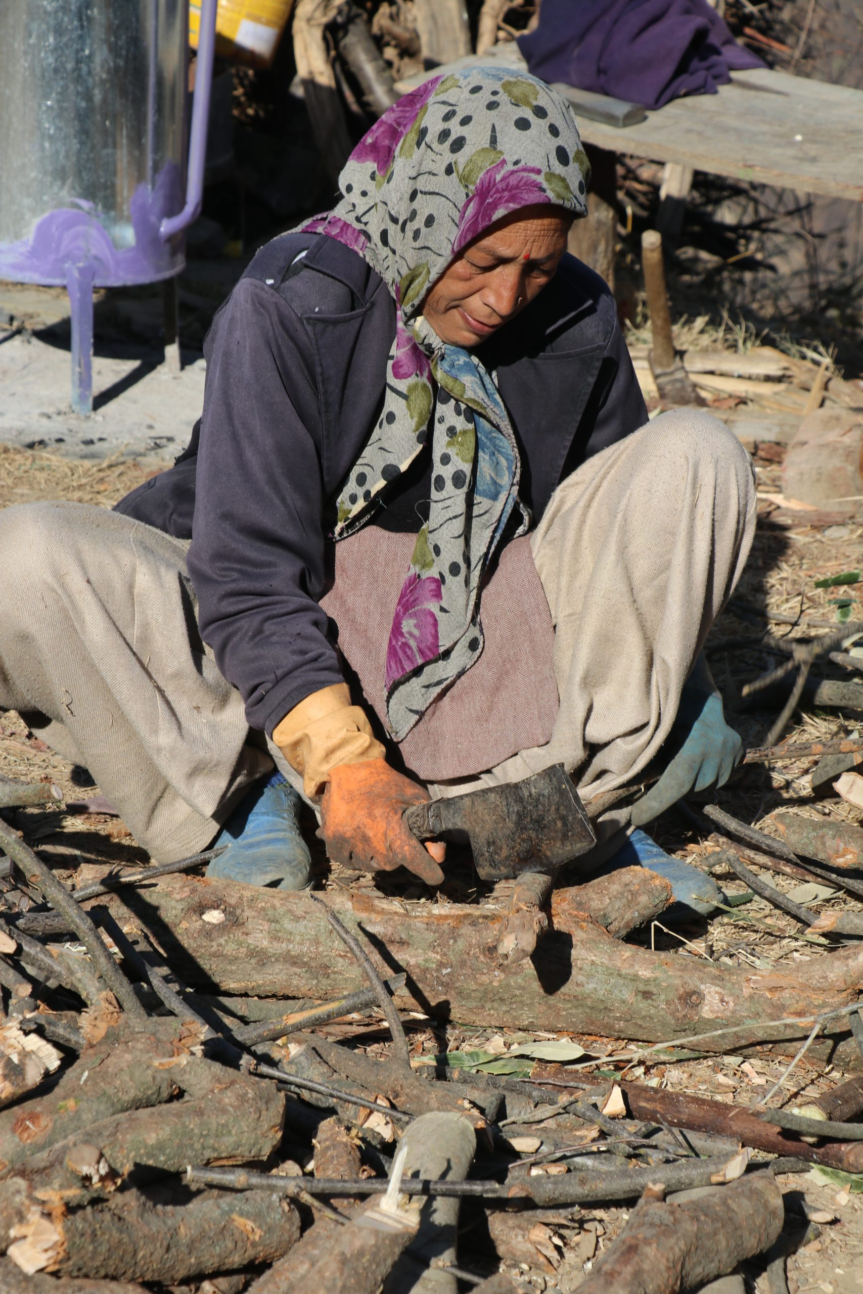 A village woman cutting woods with a blade