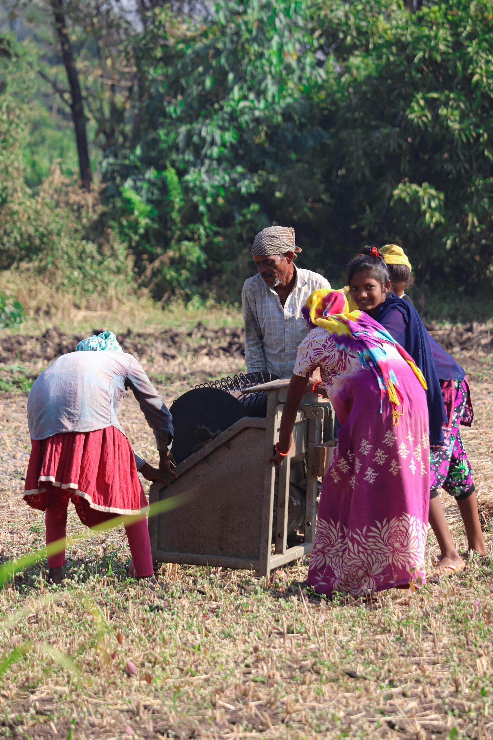 Farmers lifting a machine