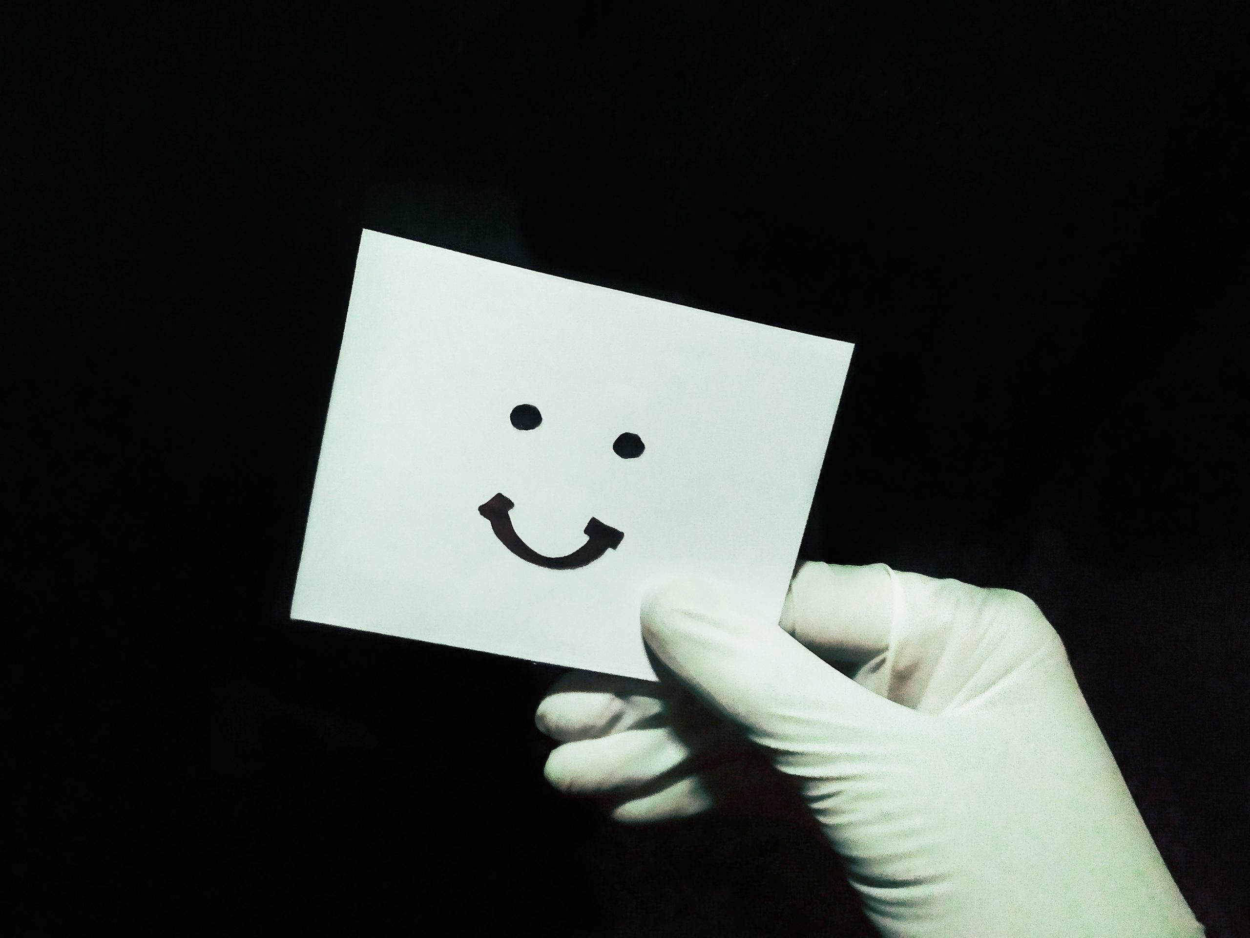 Hand showing card of happy smiley