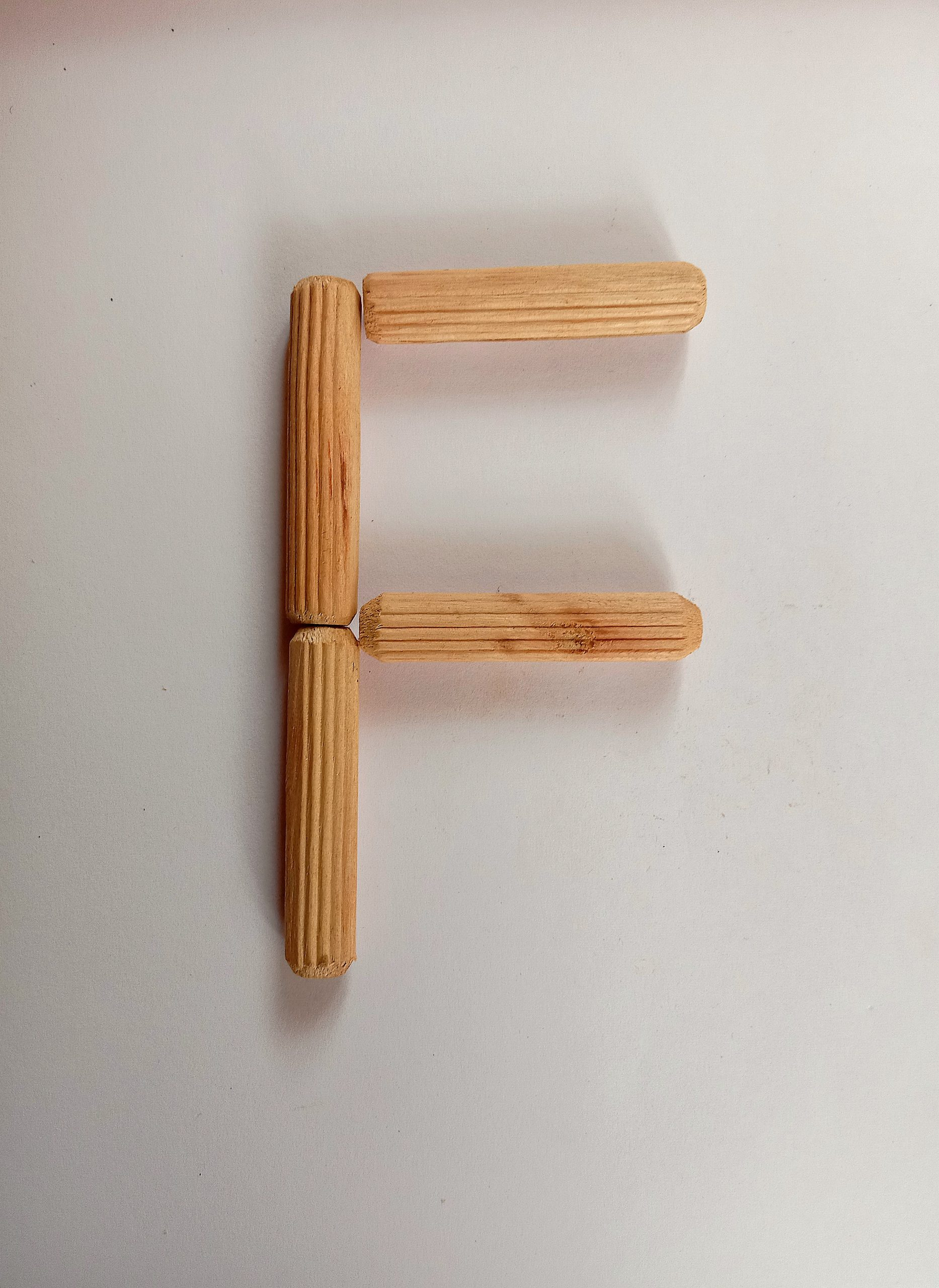 Letter F written with sticks