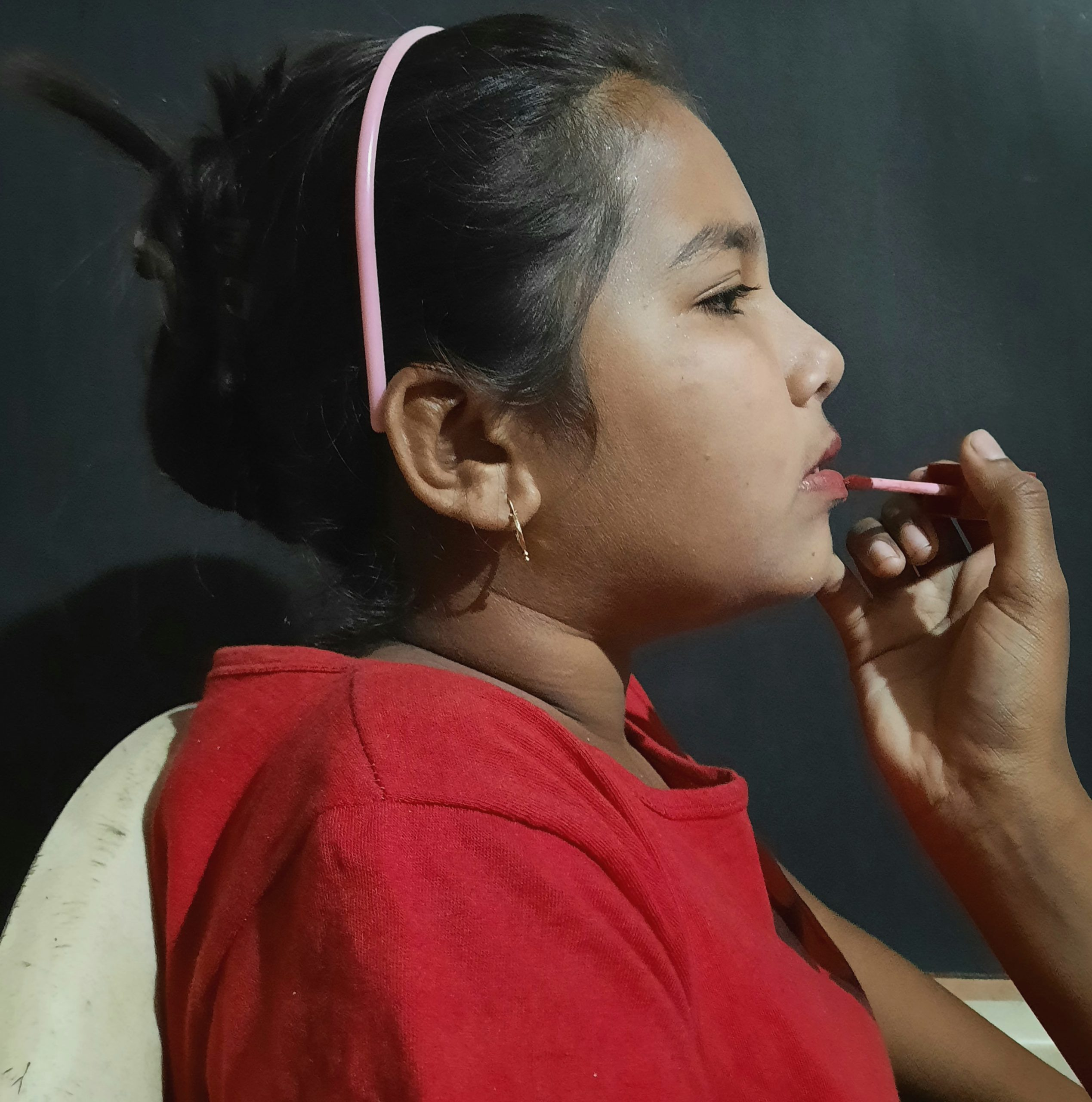 A girl applying lip color