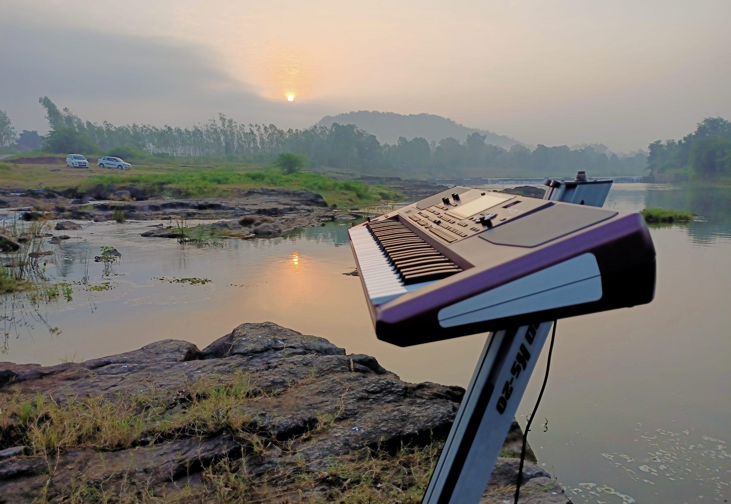 Music keyboard on rock near river