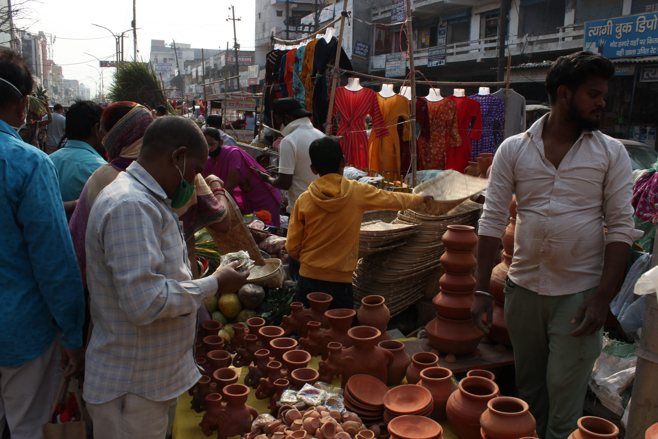 People purchasing clay pots in a market