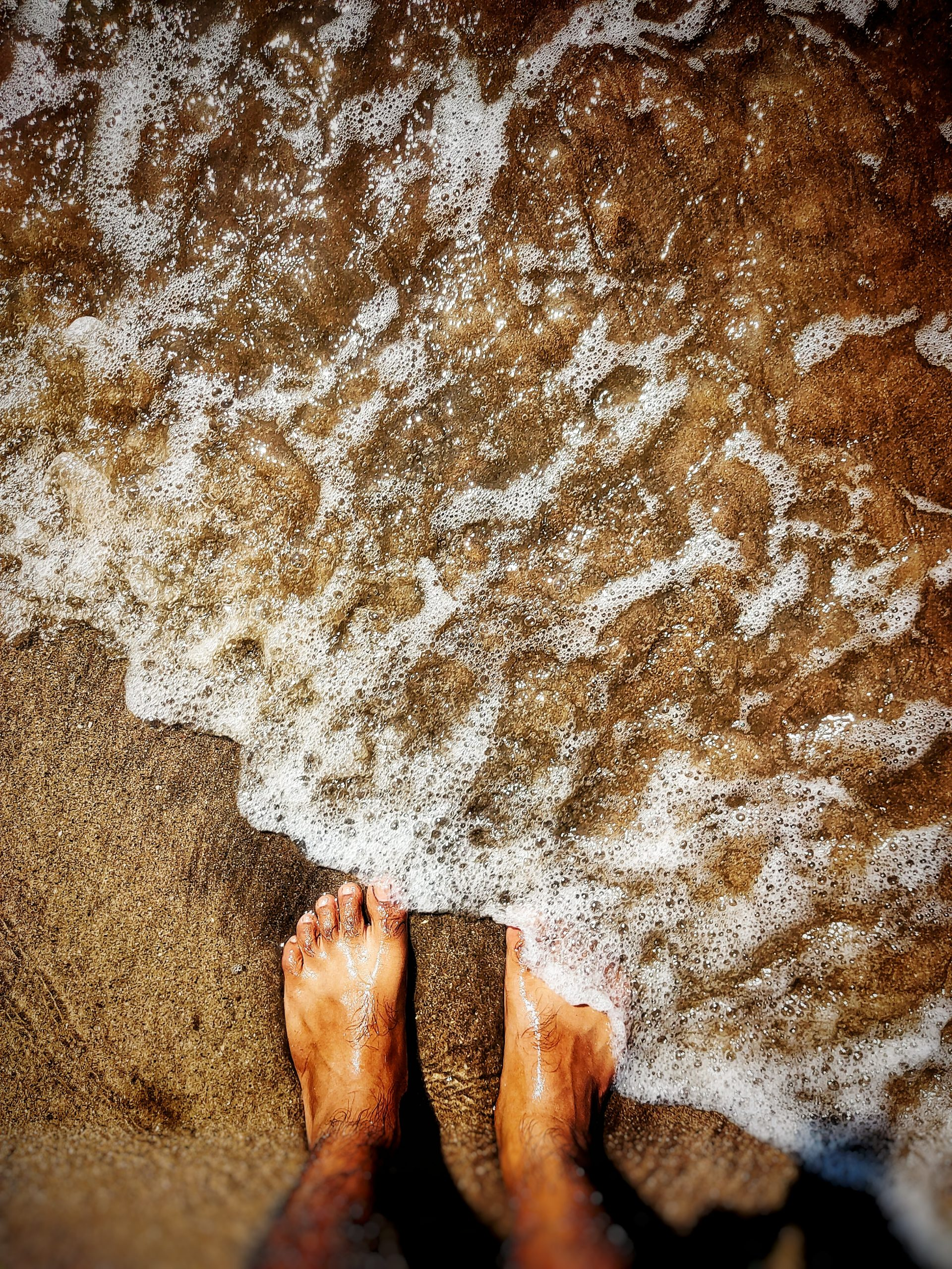 Beach water splashing on a mans feet