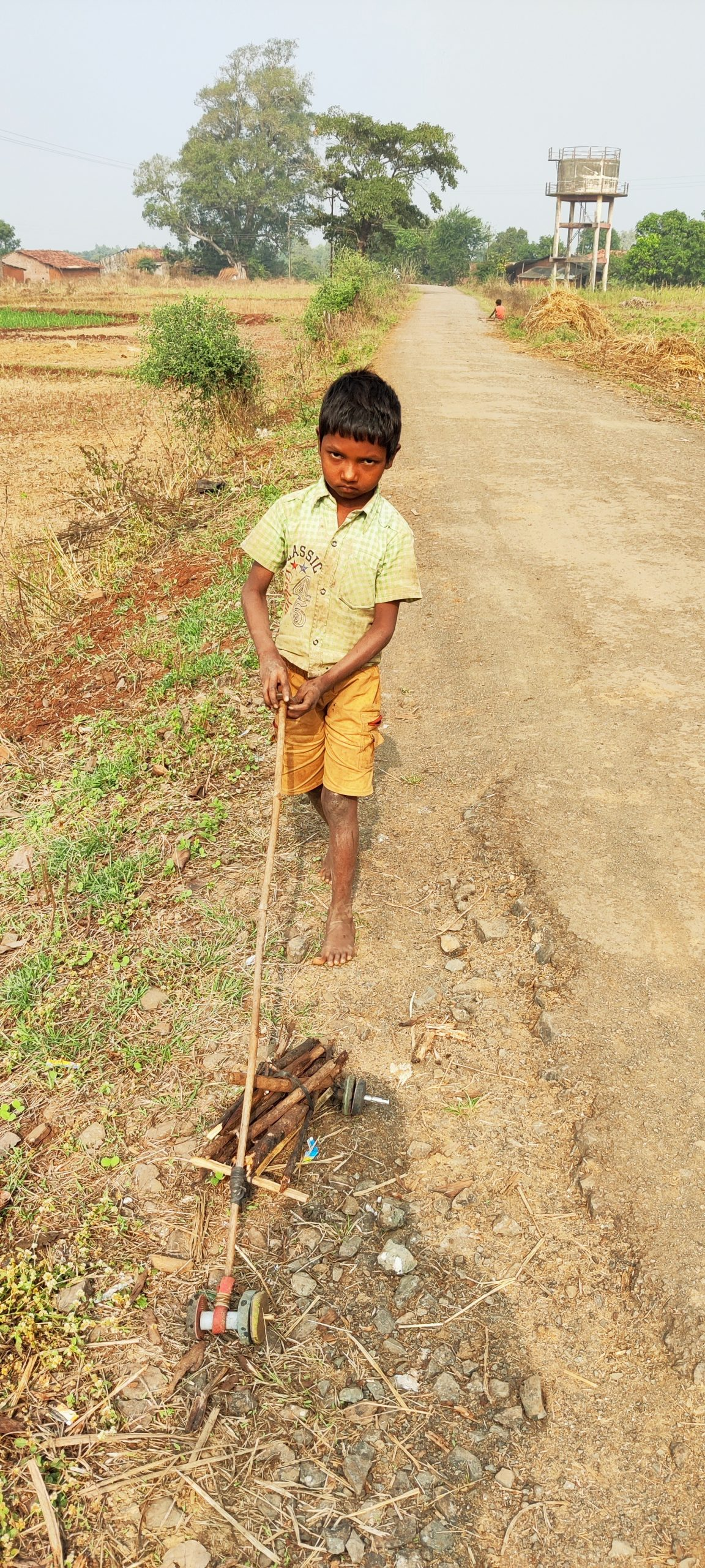 Boy rooling his wooden toy on ground in the farm