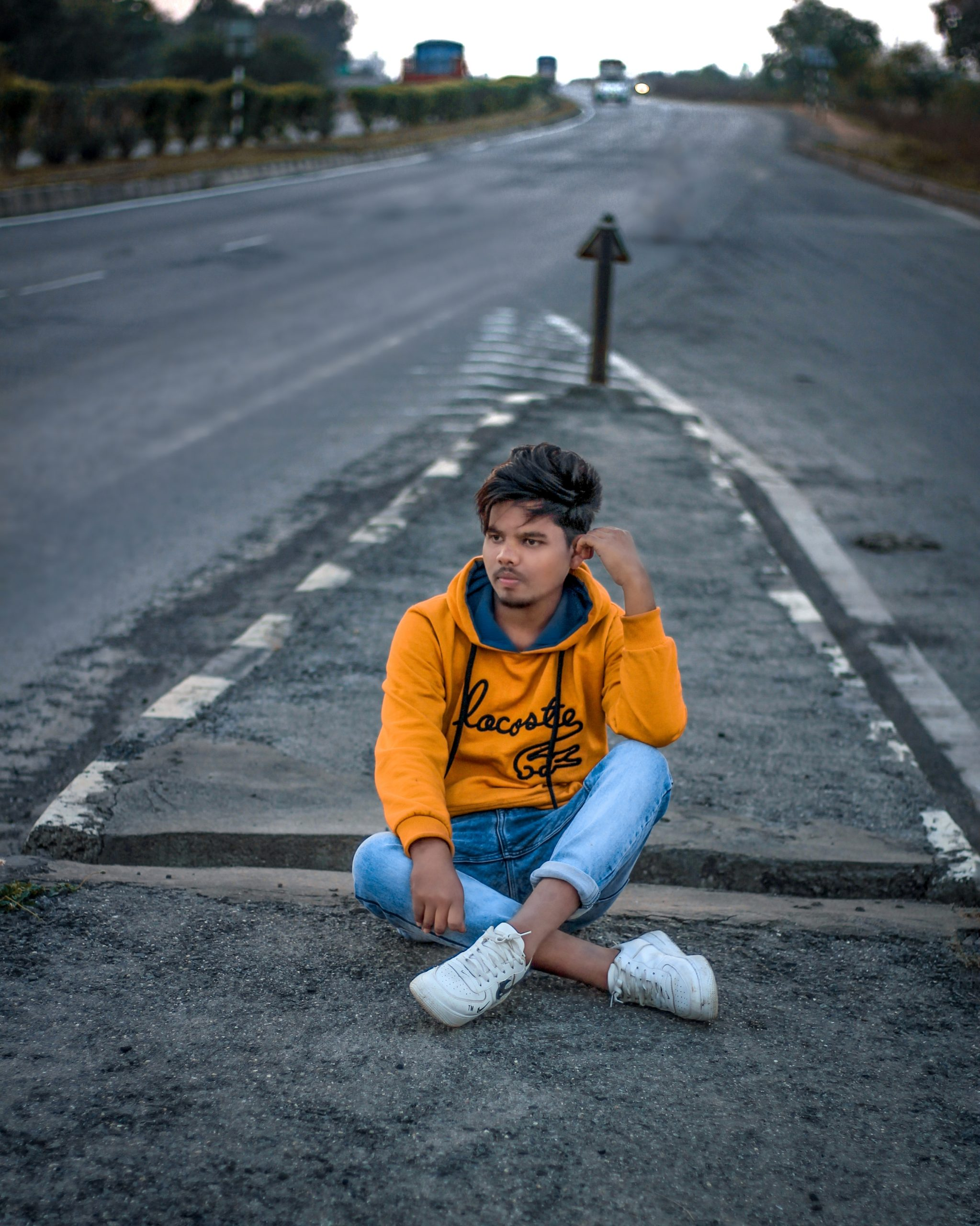 A boy sit on a road