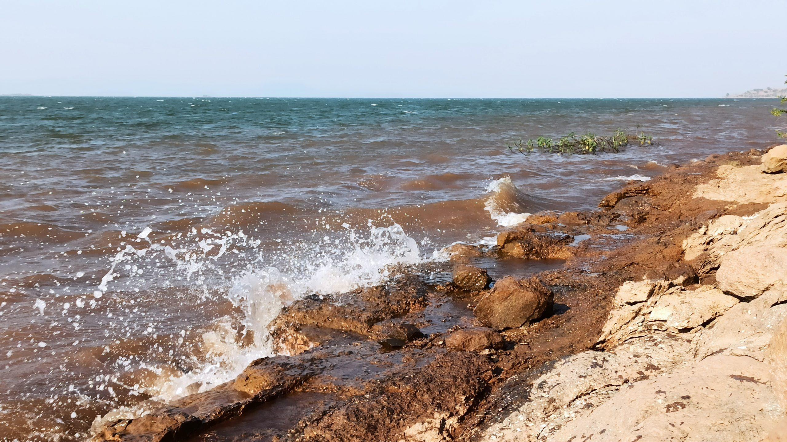 Beach water splashing on the rocks at shore
