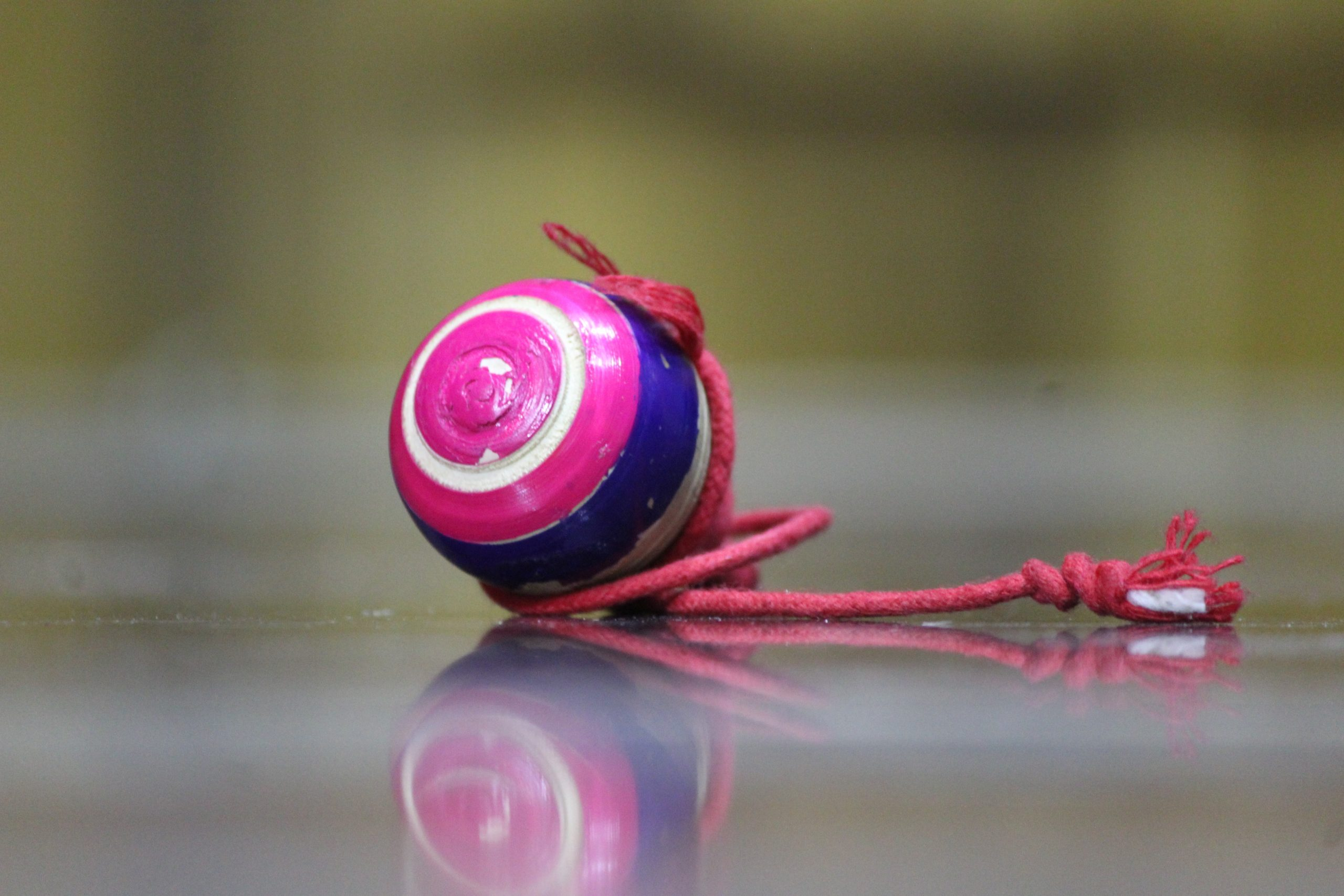Pink spinning top with a thread