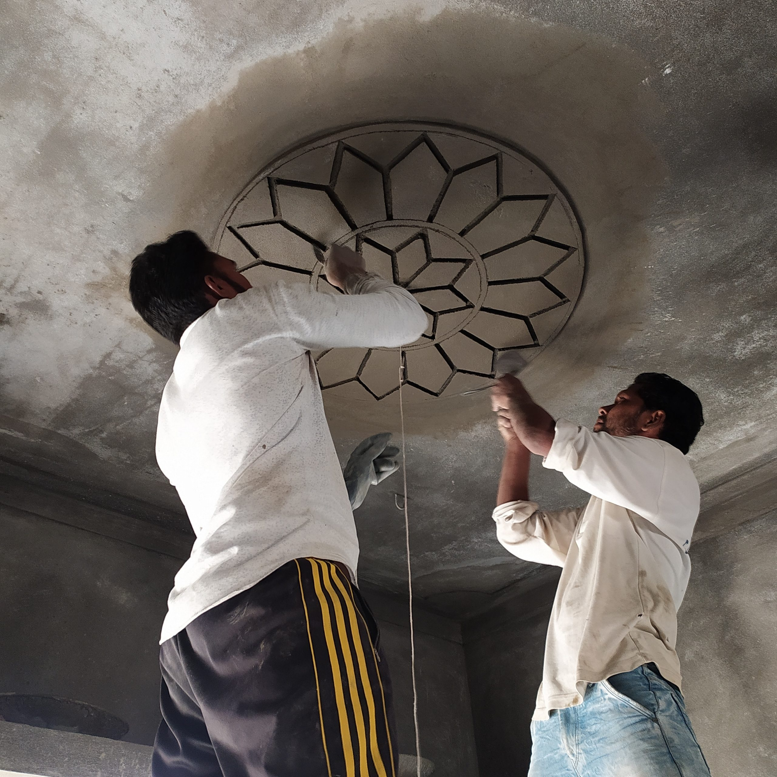 Workers making a floral design on a roof