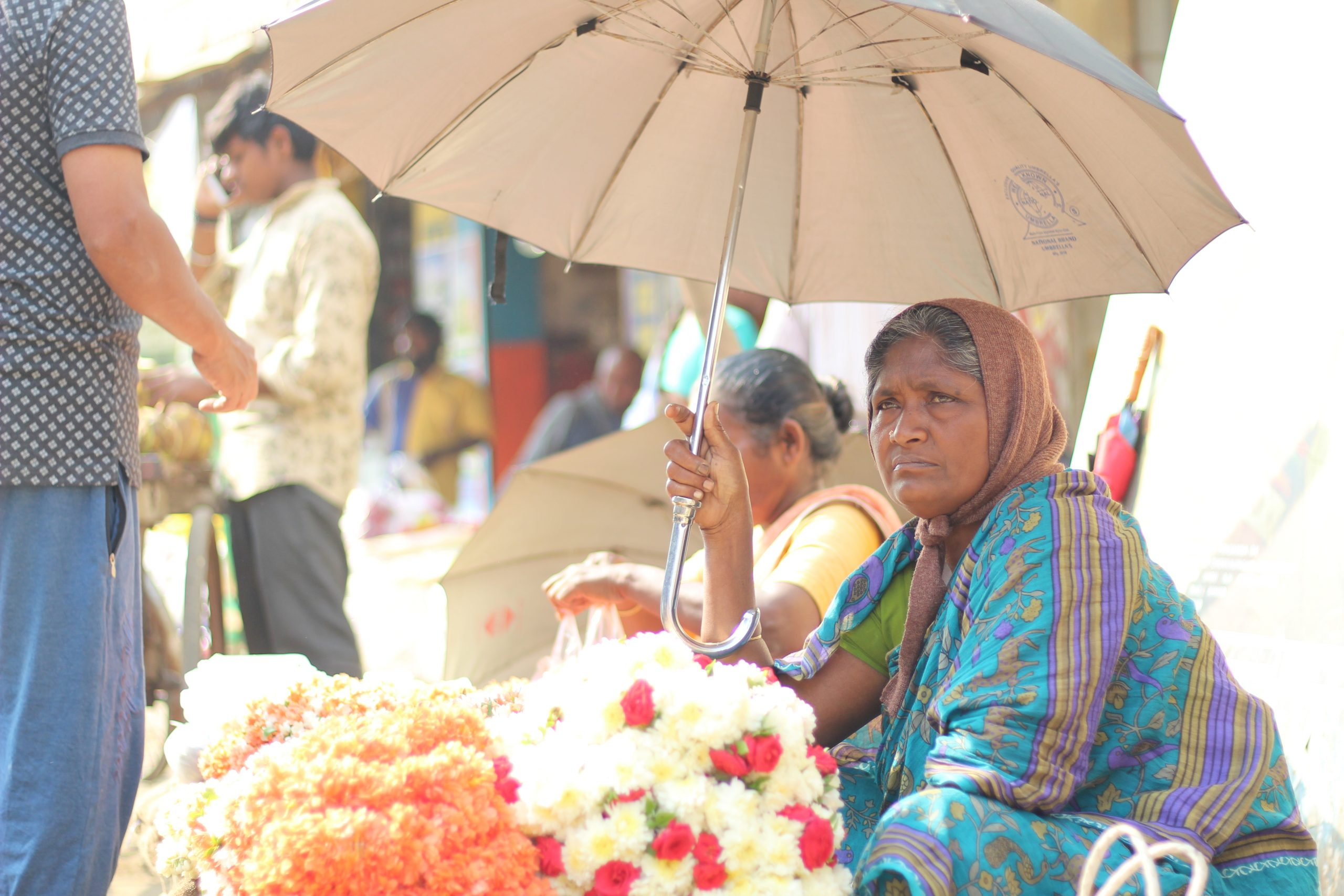 Women selling flowers and sitting under umbrella
