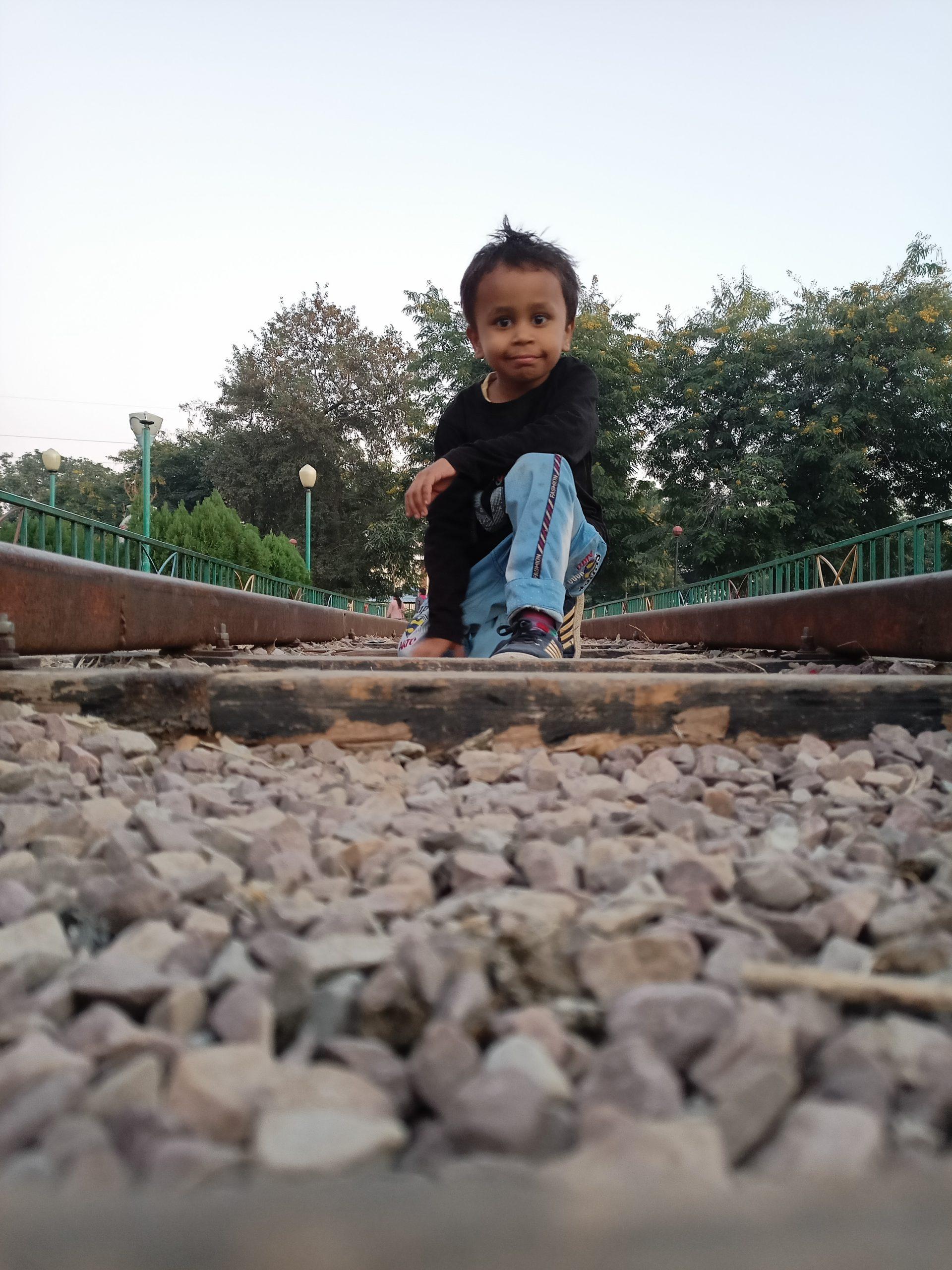 A kid posing on a railway track