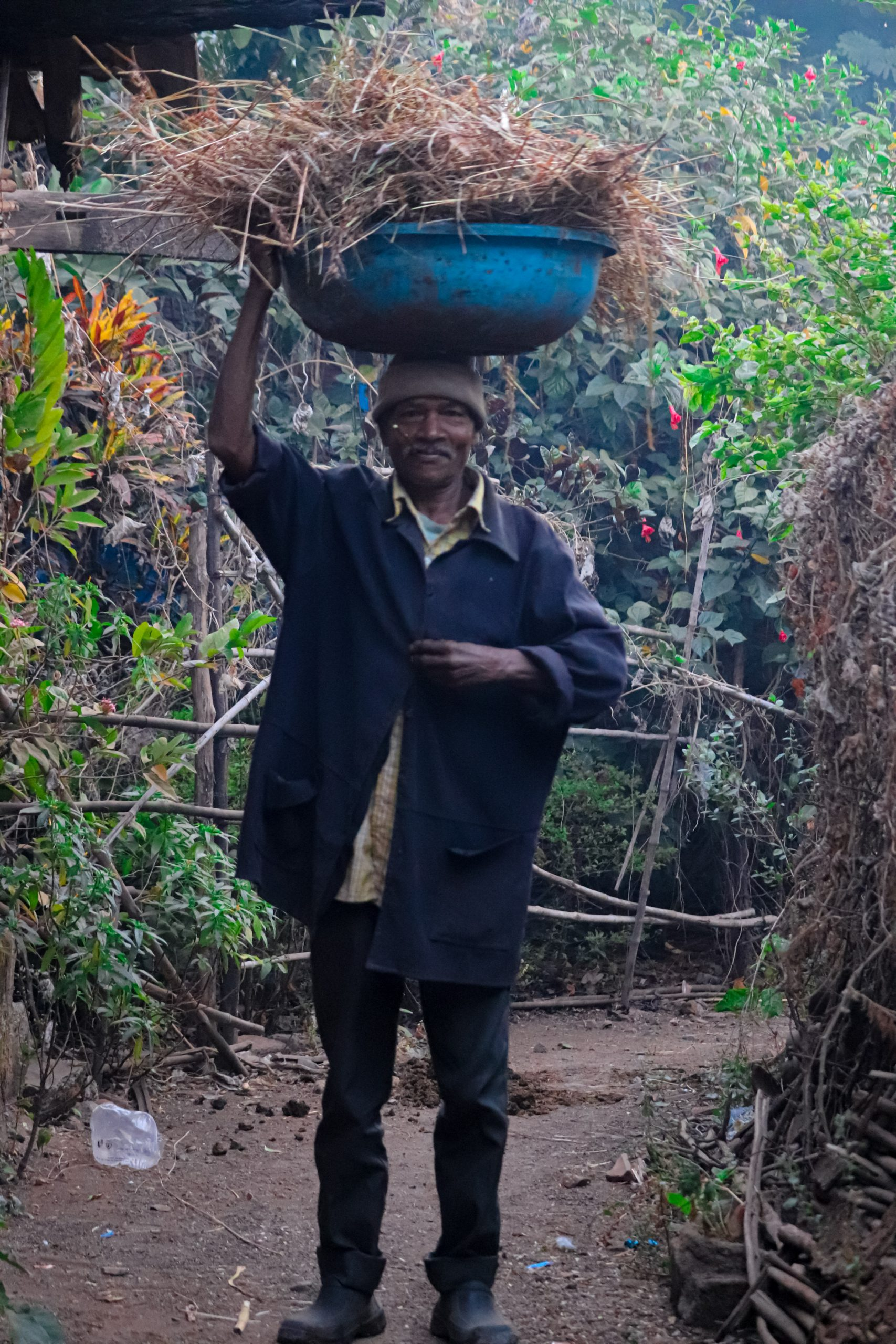 A village man carrying waste basket
