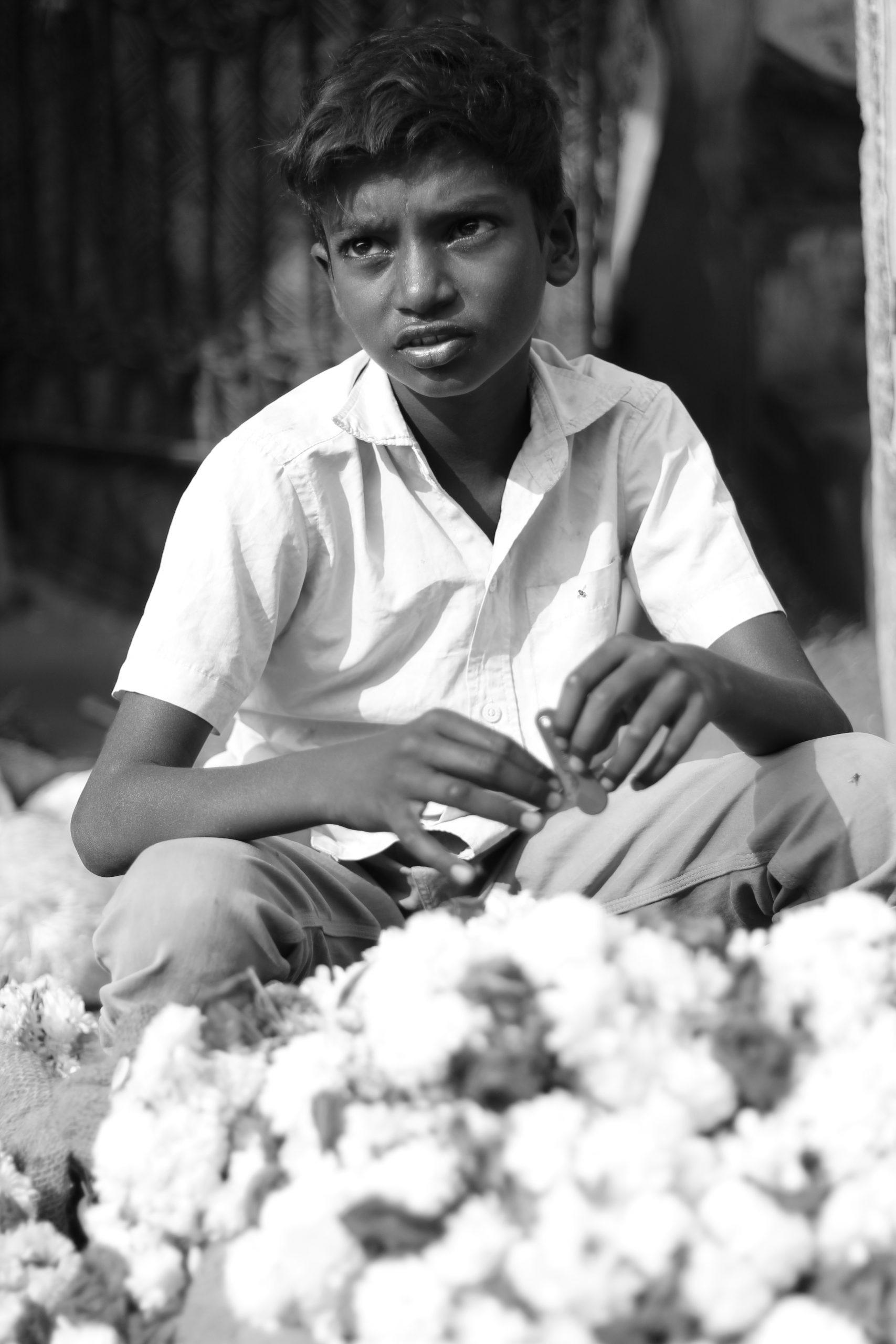 A boy selling cut flowers