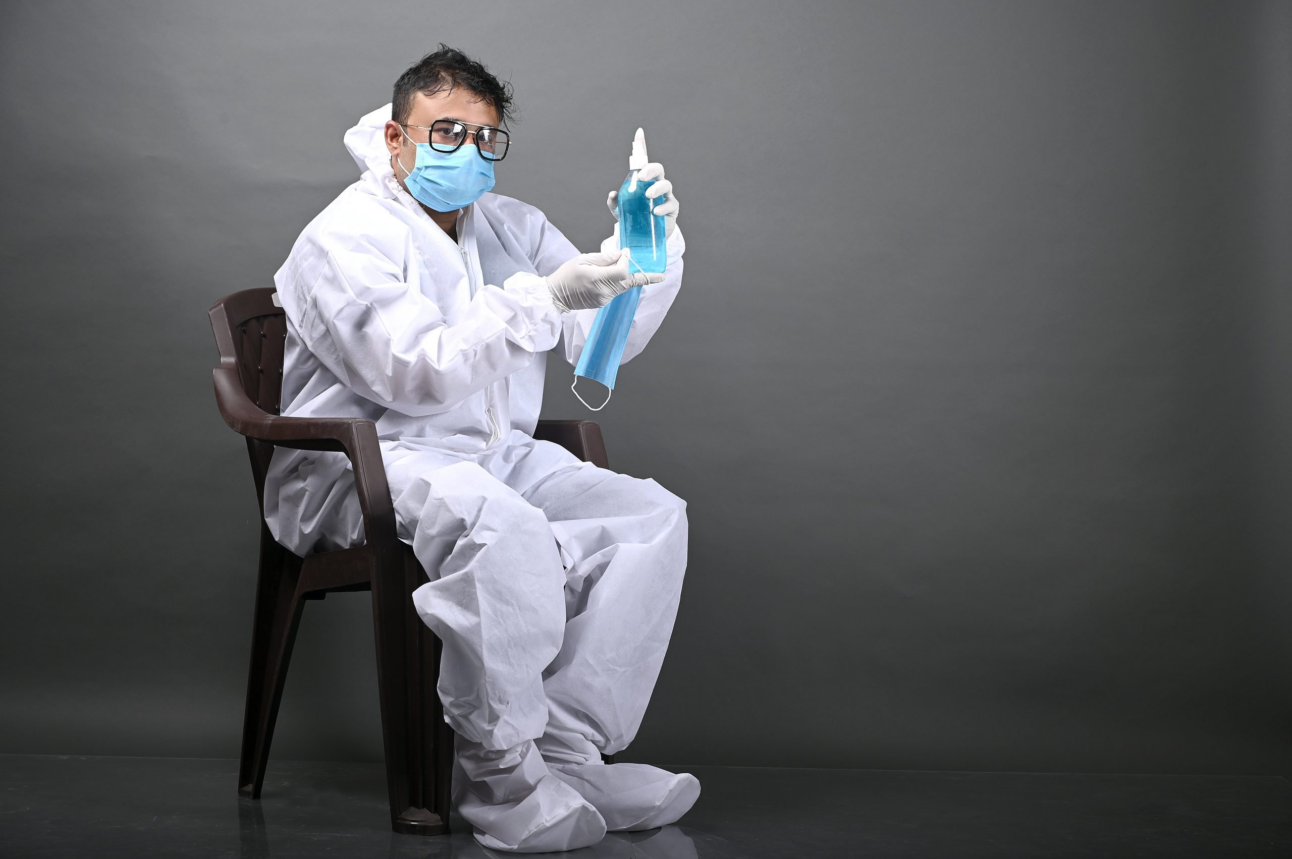 Man wearing PP kit and sanitizer in his hand
