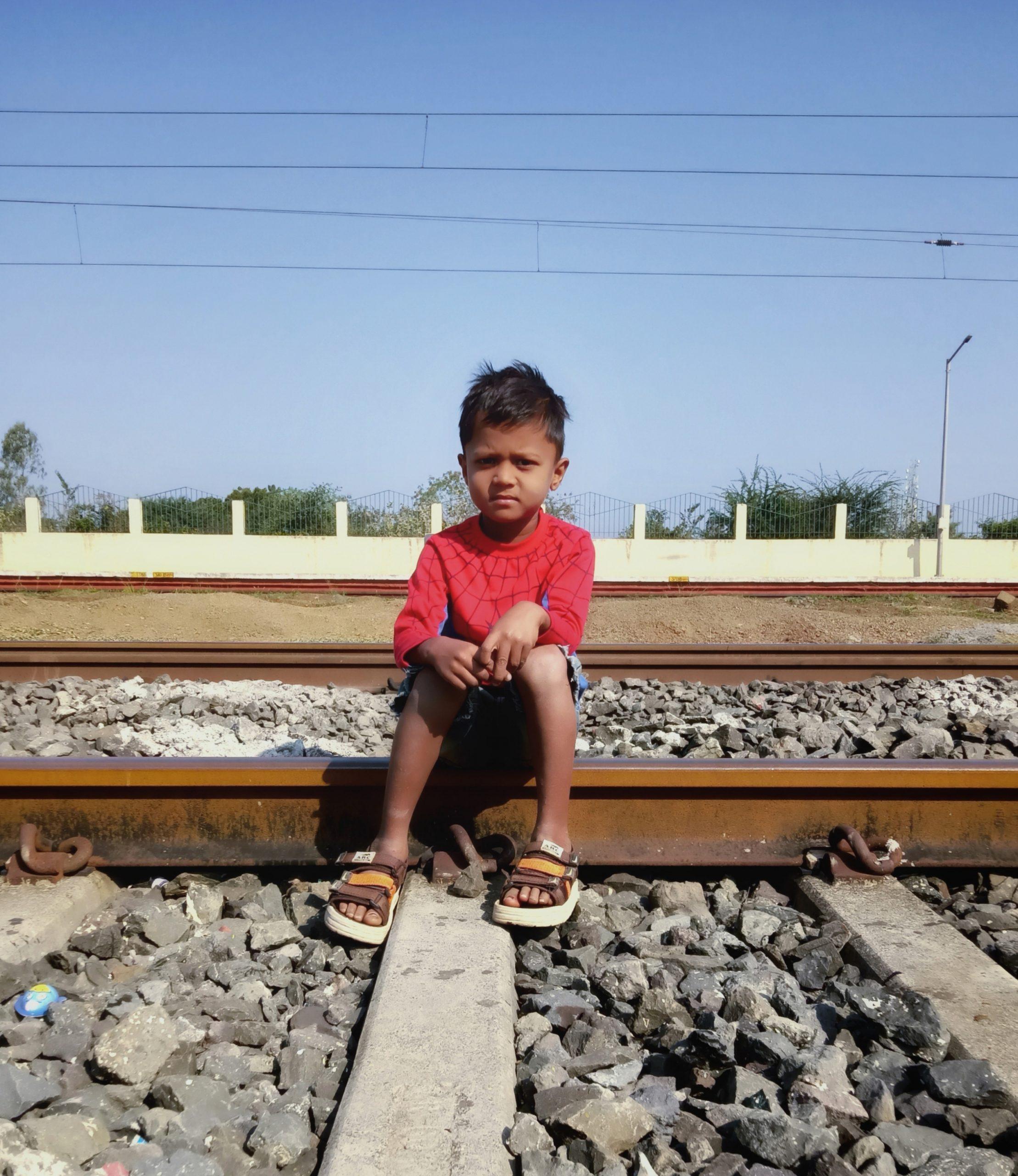 A kid sitting on railway track