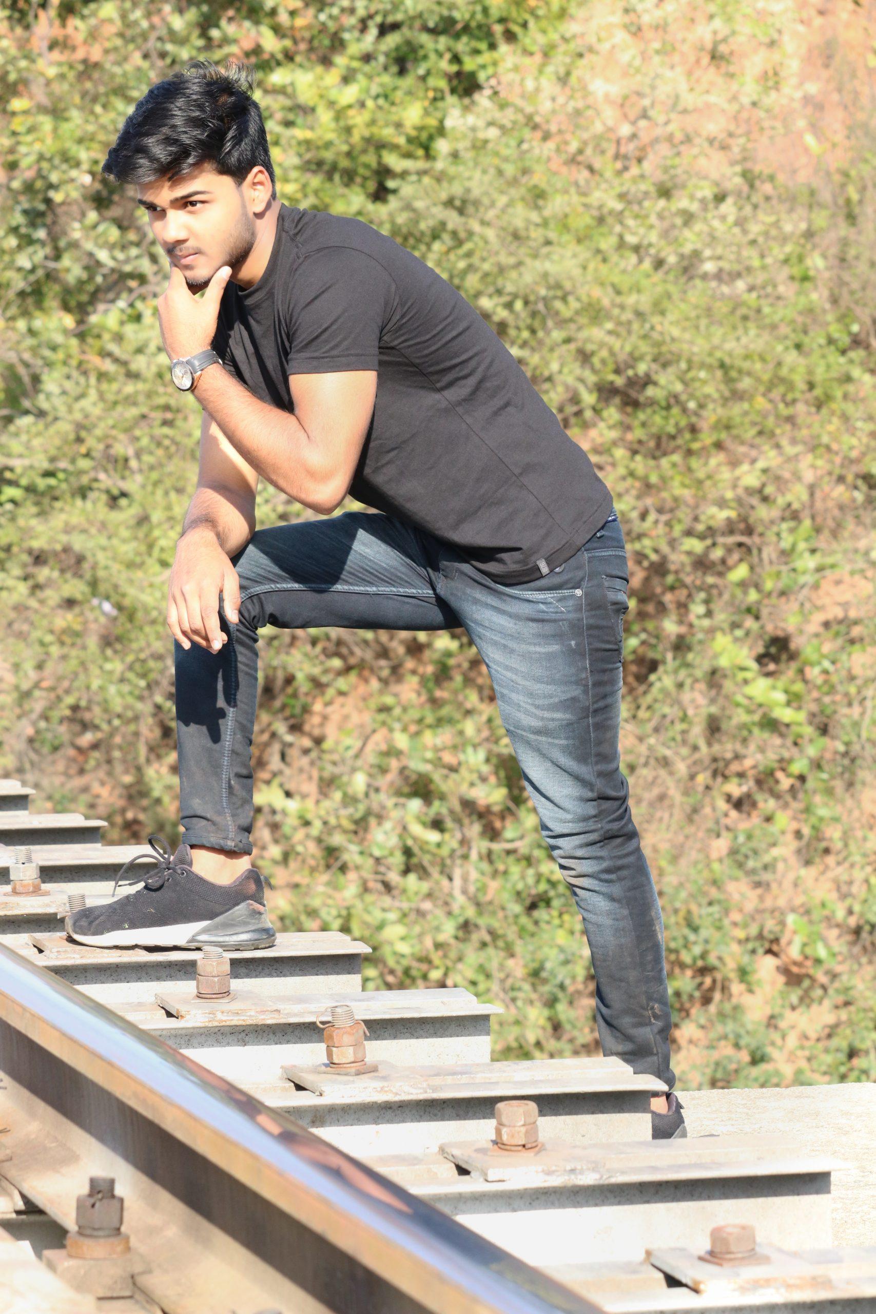 A stylish boy near railway track