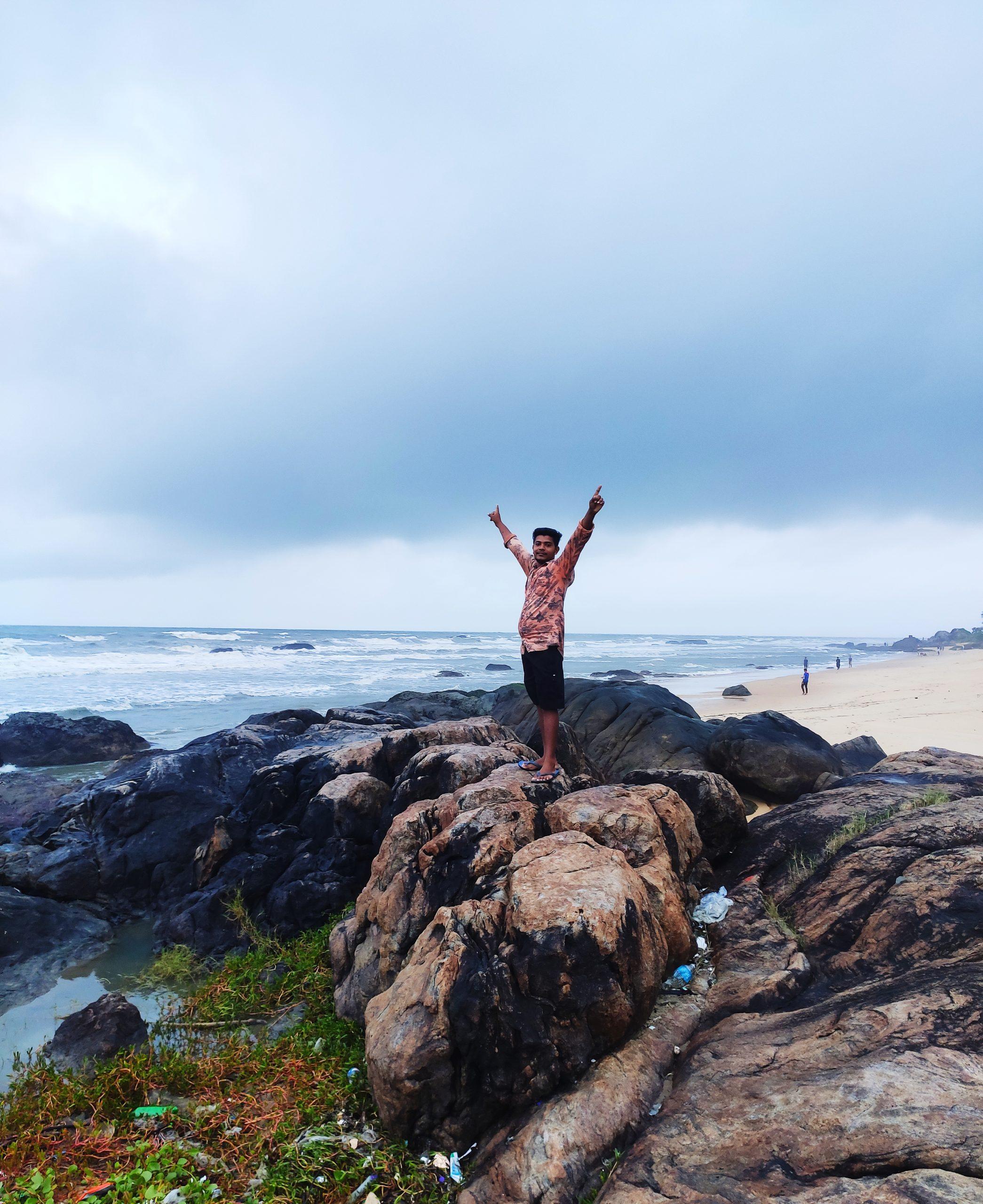 man posing on rocks at the sea