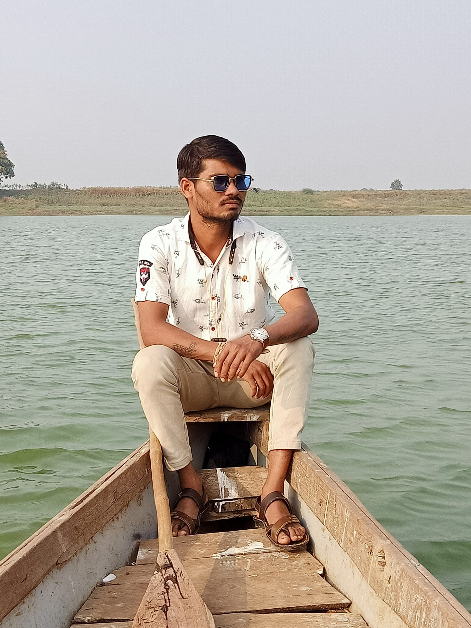 Boy giving pose while sitting in the boat