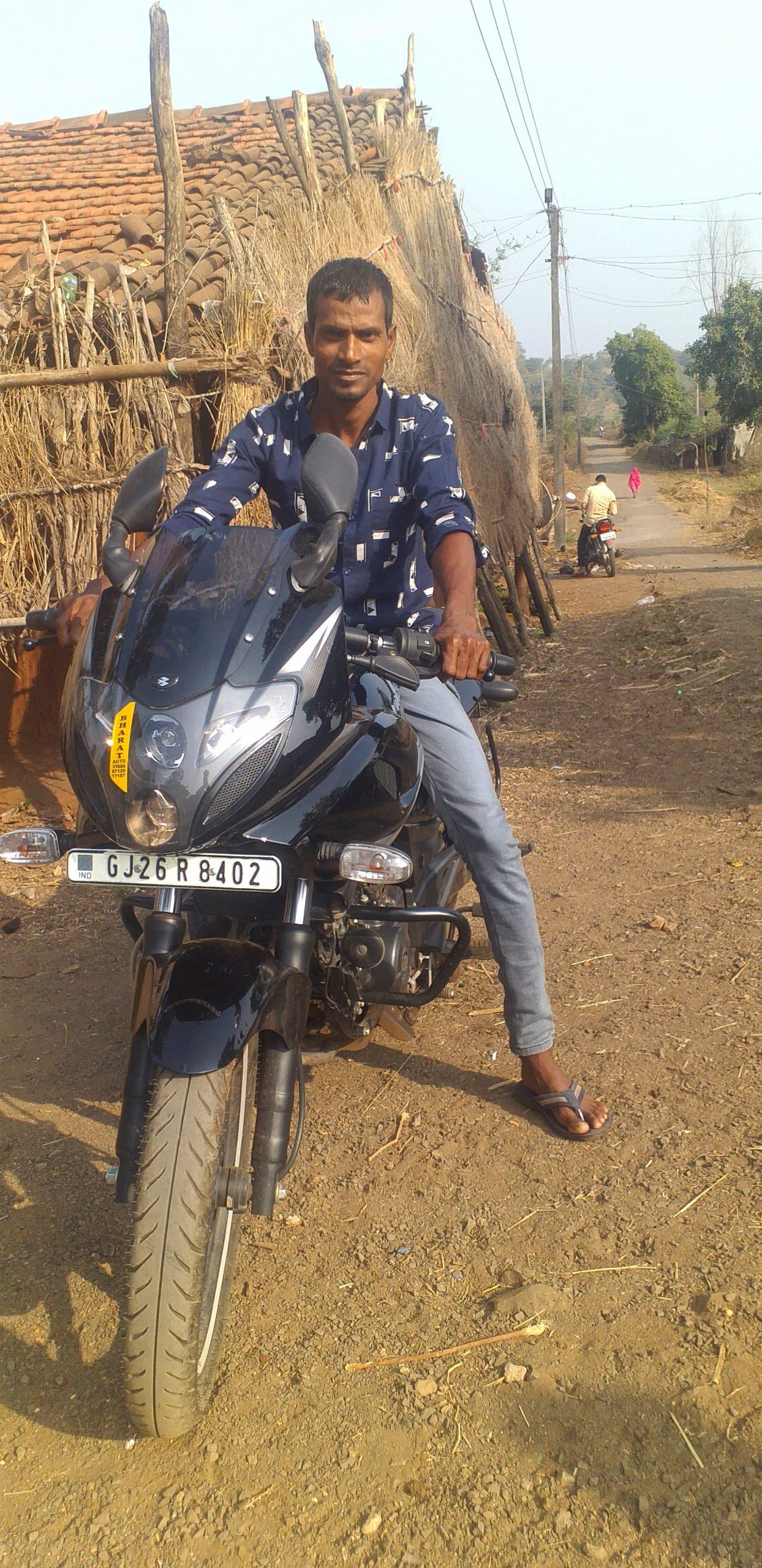Boy posing bike near hut in village