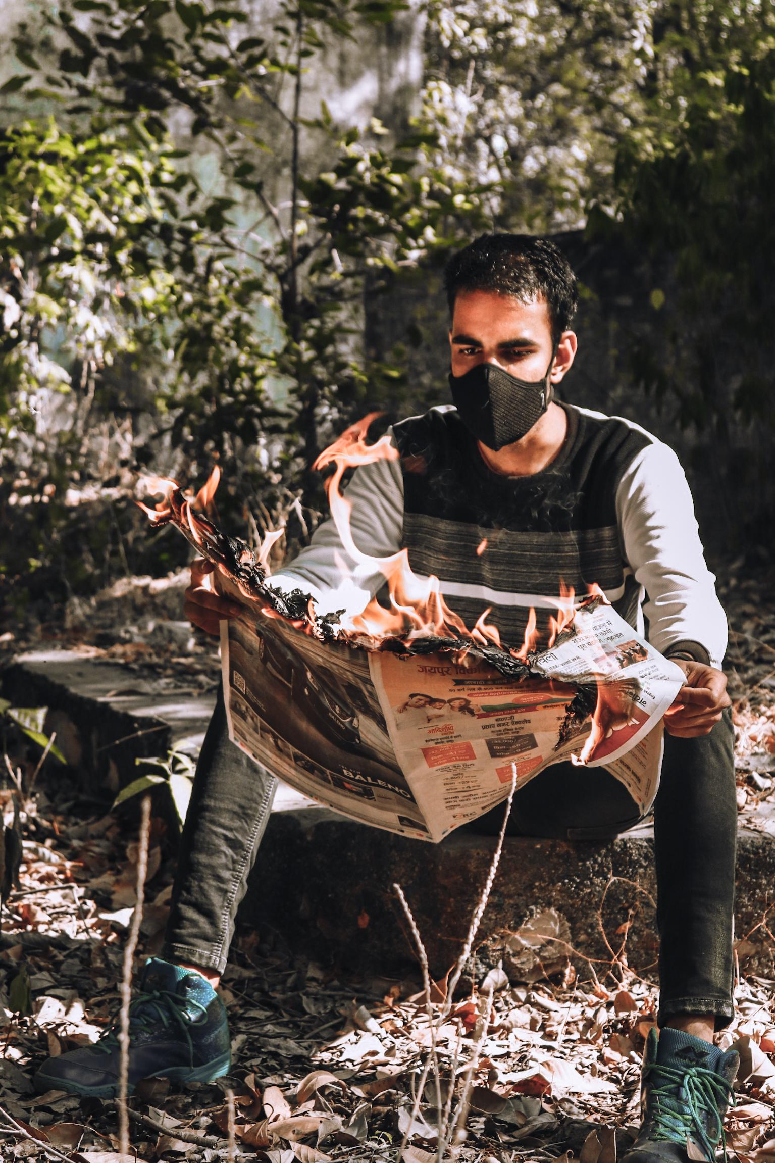Boy holding burning newspaper
