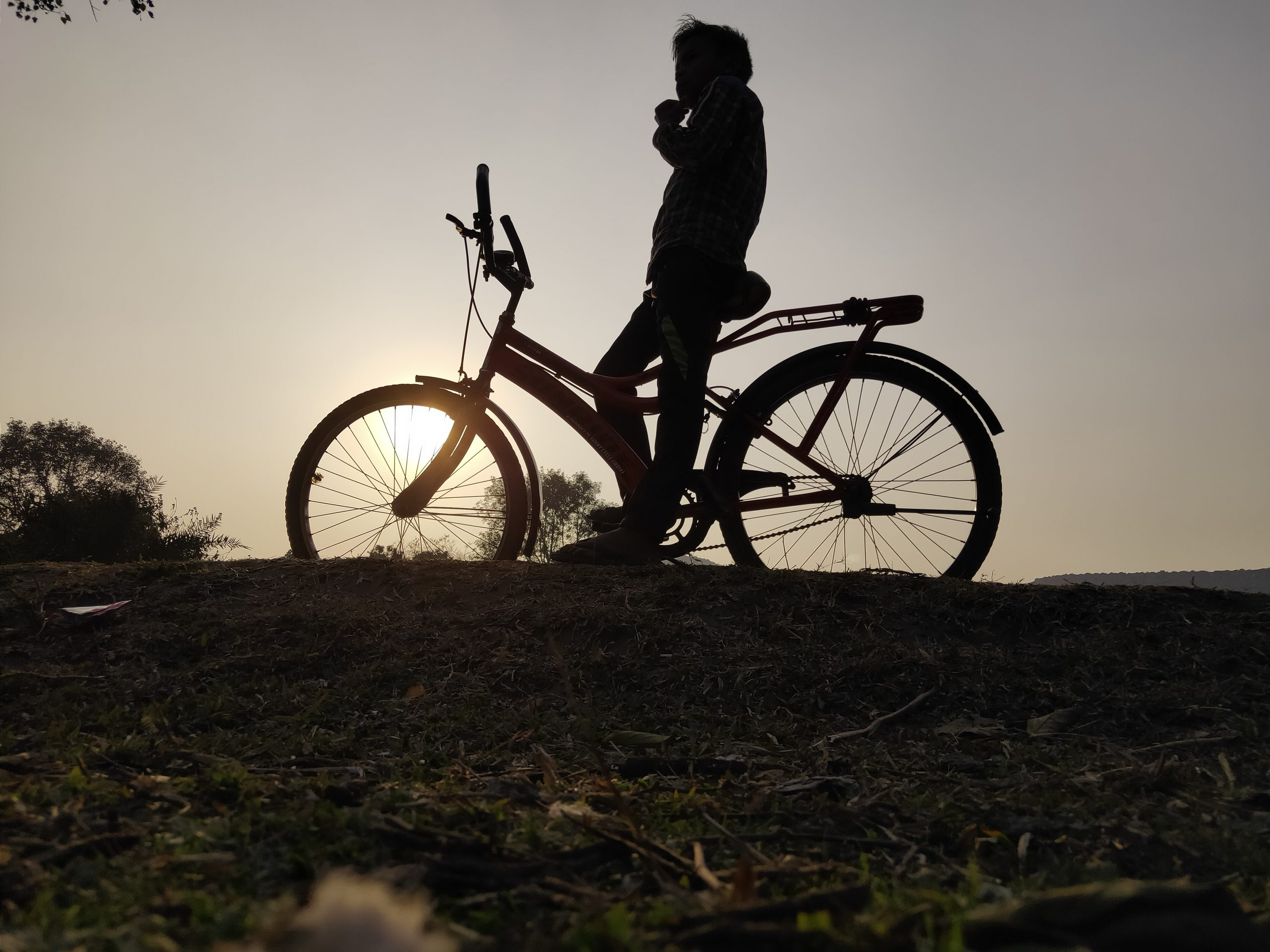 Boy on cycle in sunset