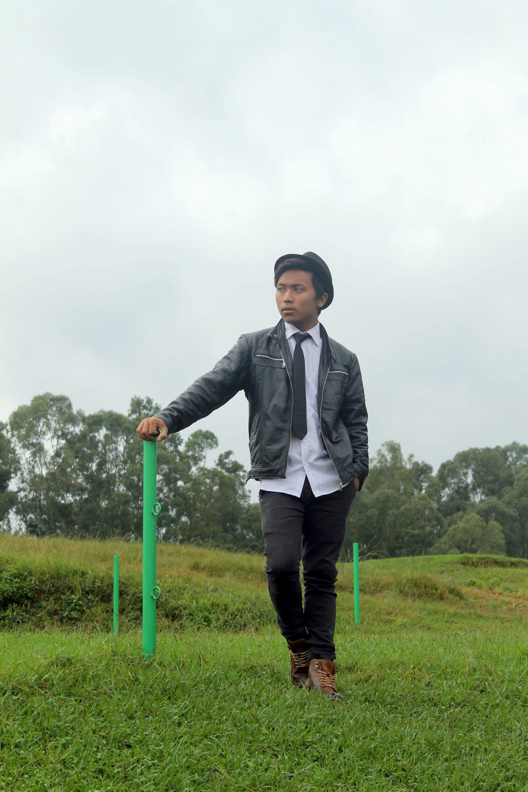 Boy posing in garden while holding pole