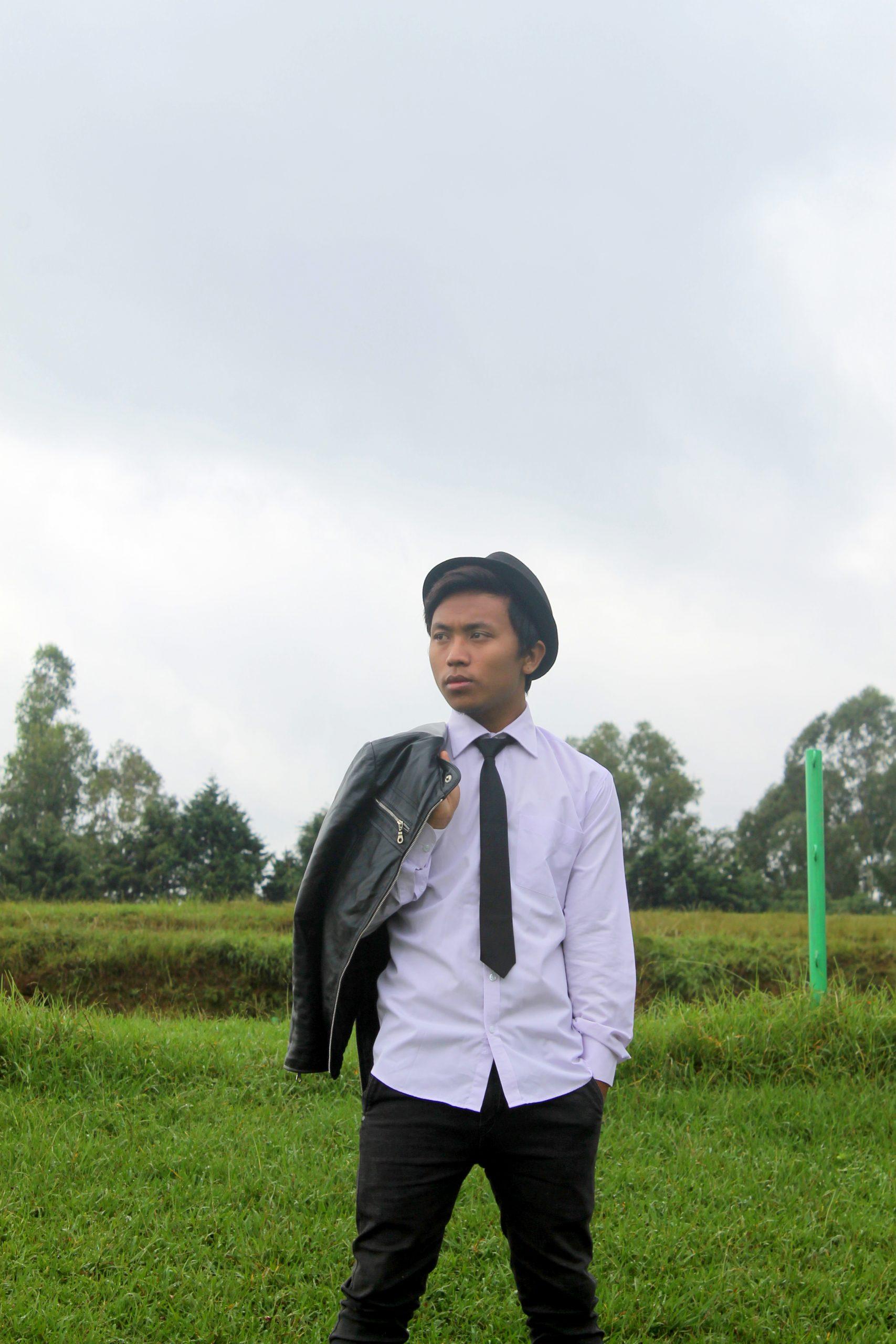 Boy posing while holding jacket