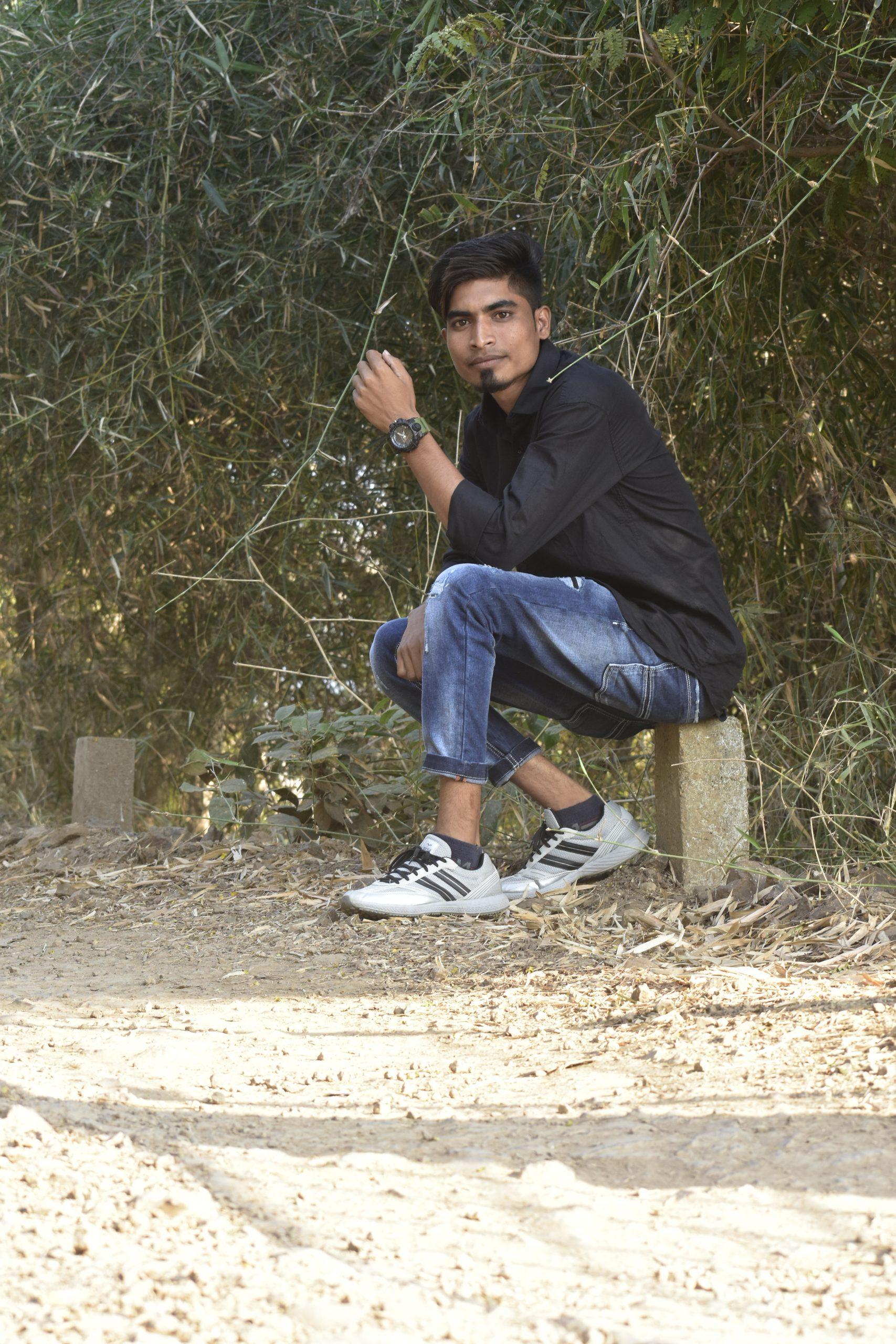 Boy posing while sitting on stone