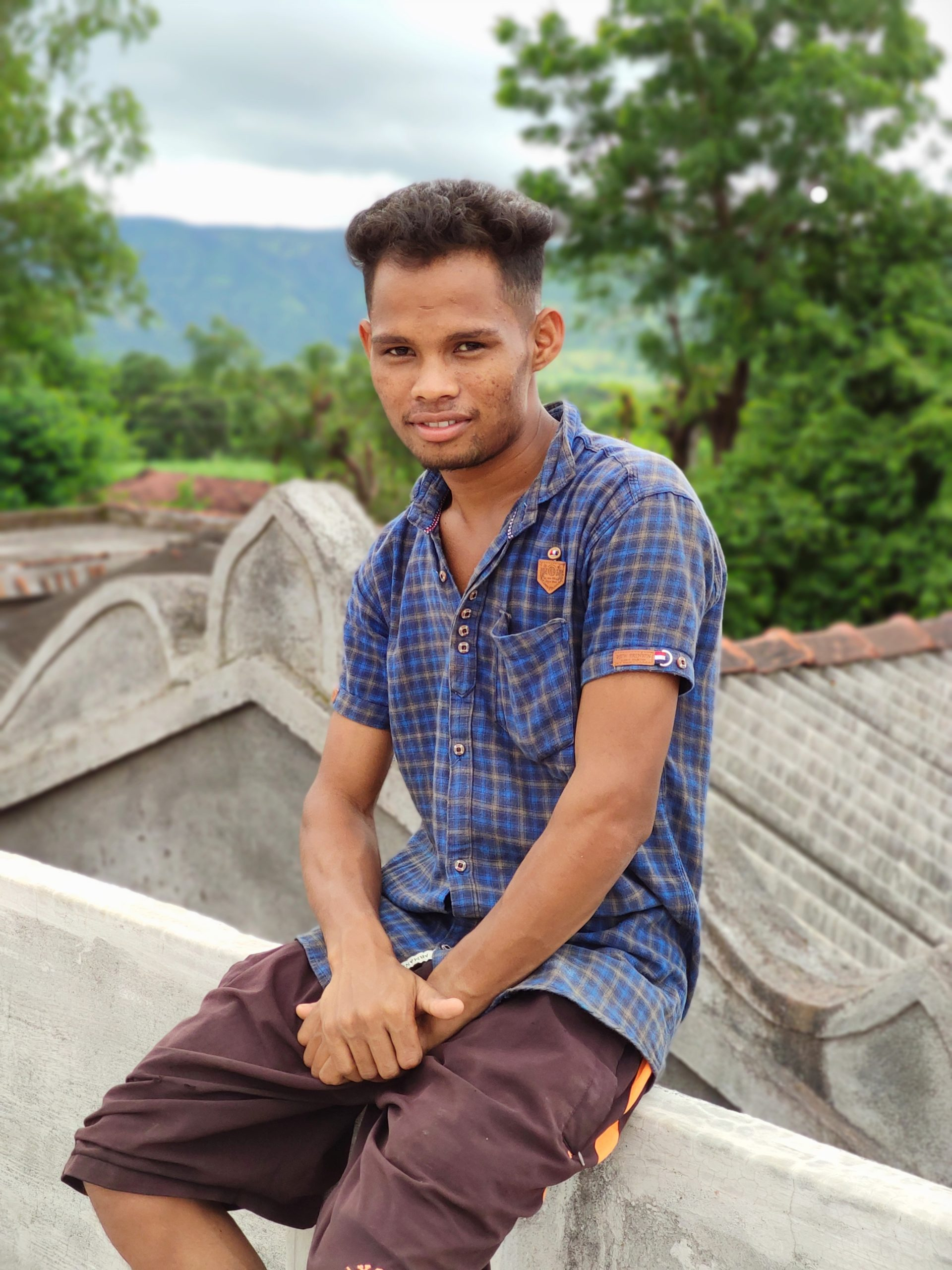 Boy sitting on house roof