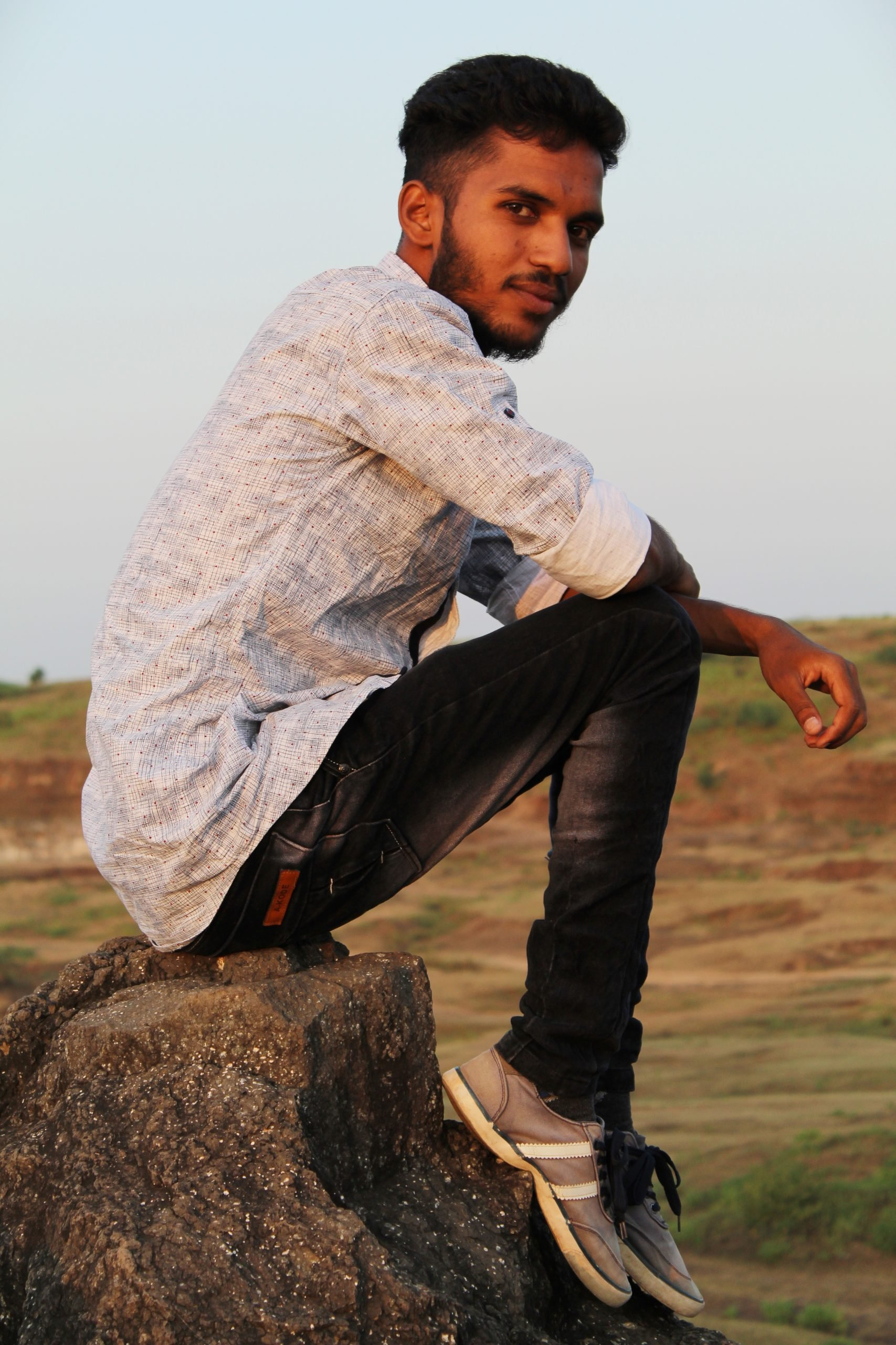 Boy sitting on rock