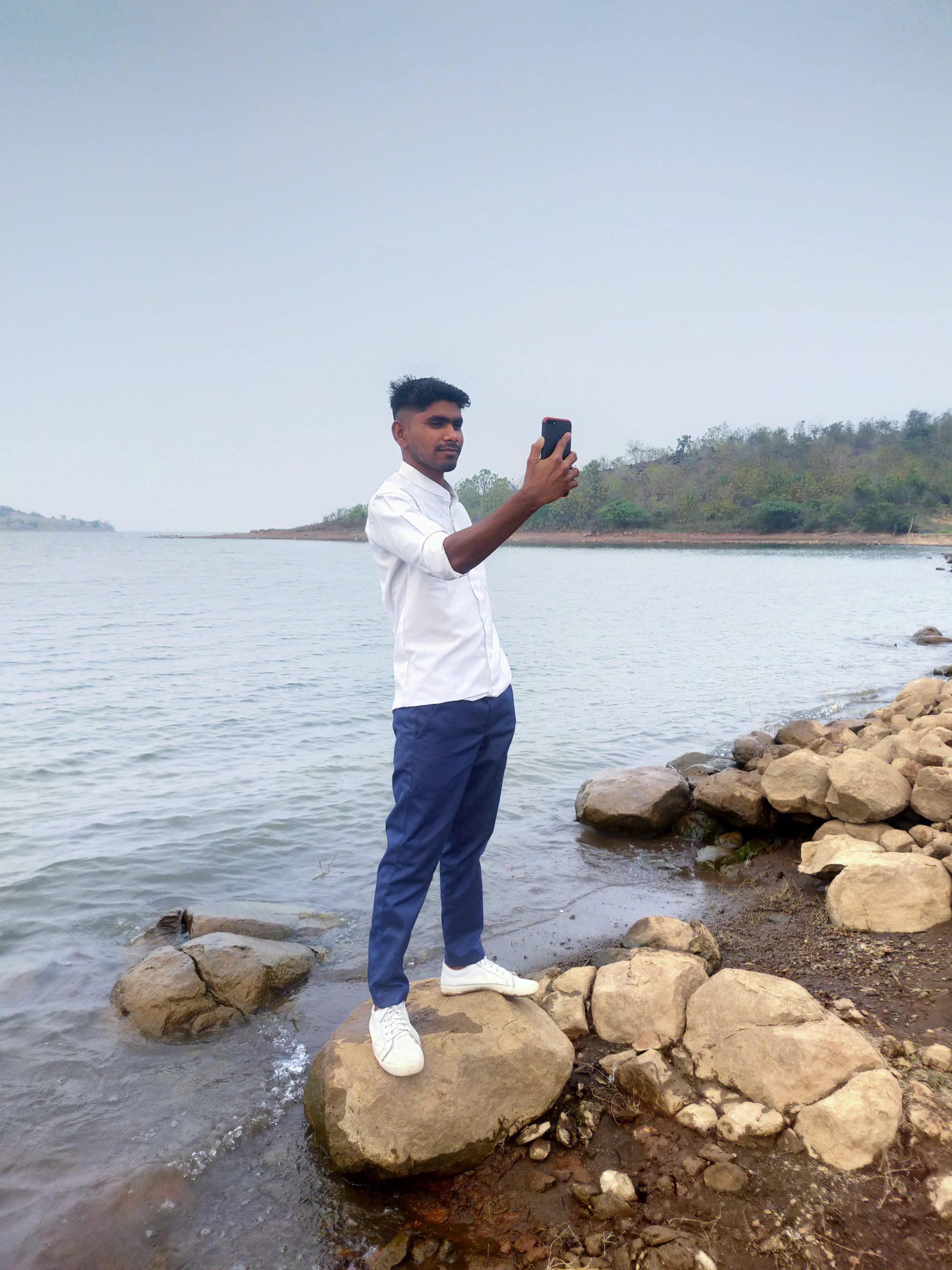 Boy taking selfie on beach