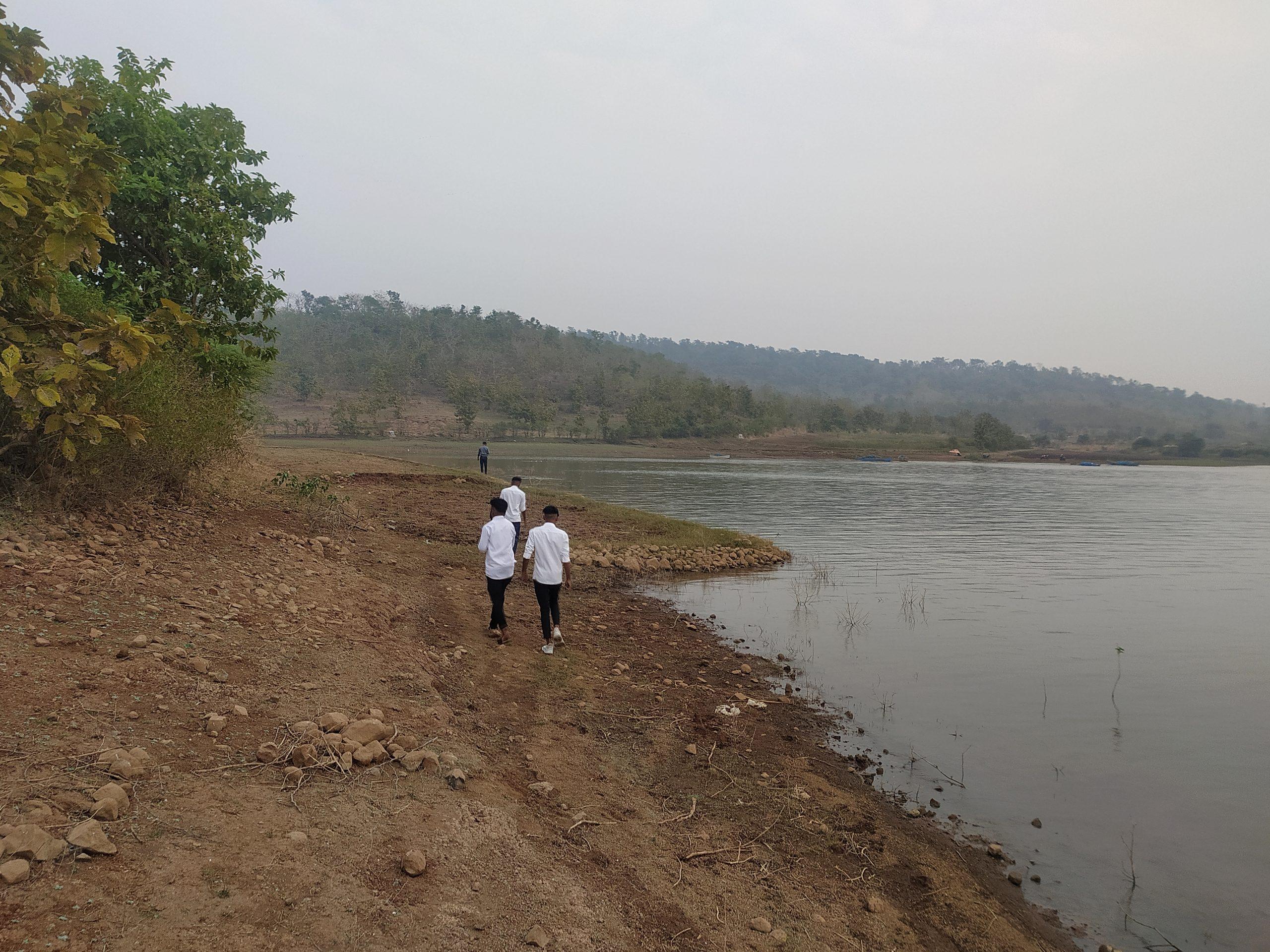Boys walking beside a lake