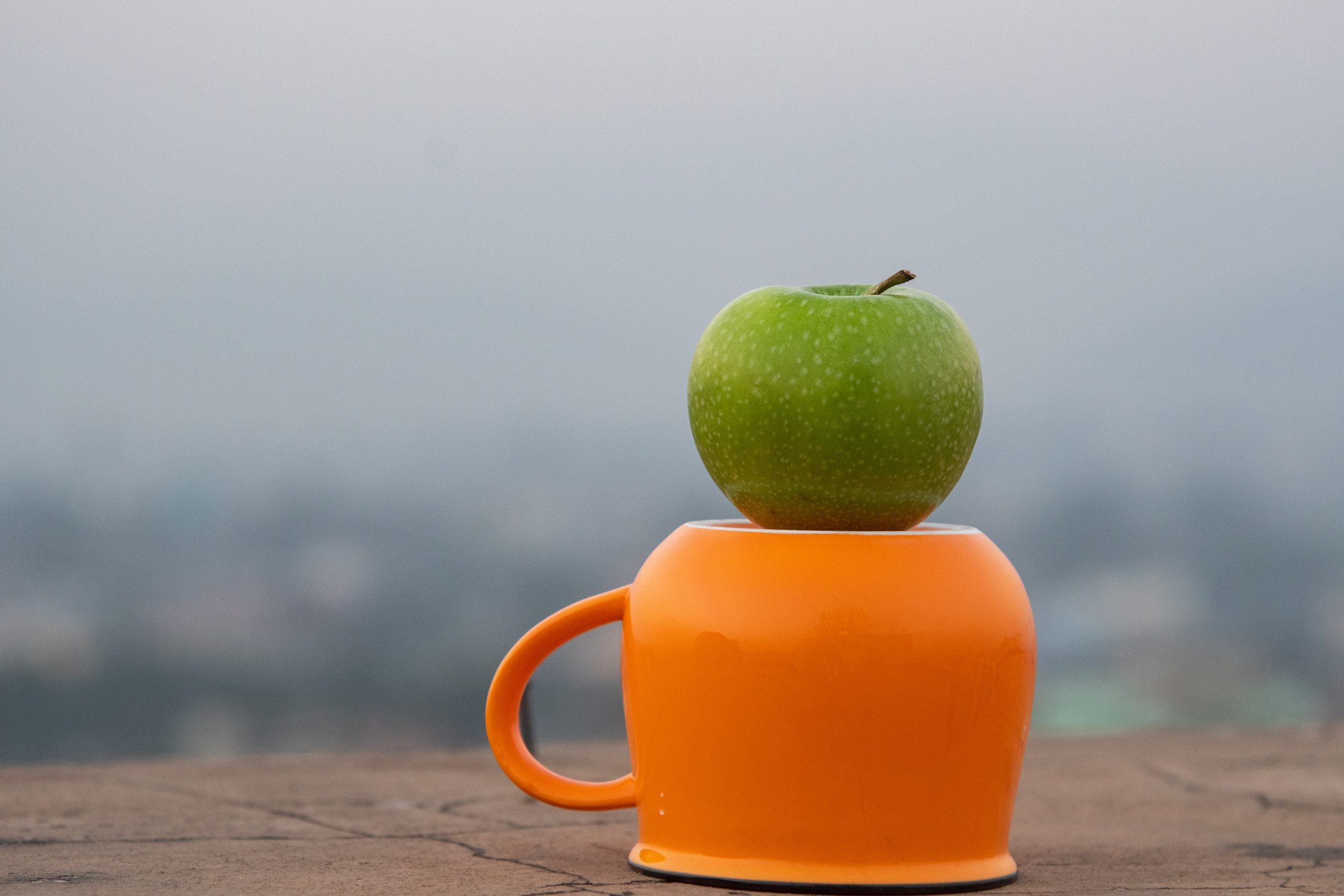 An apple on a cup