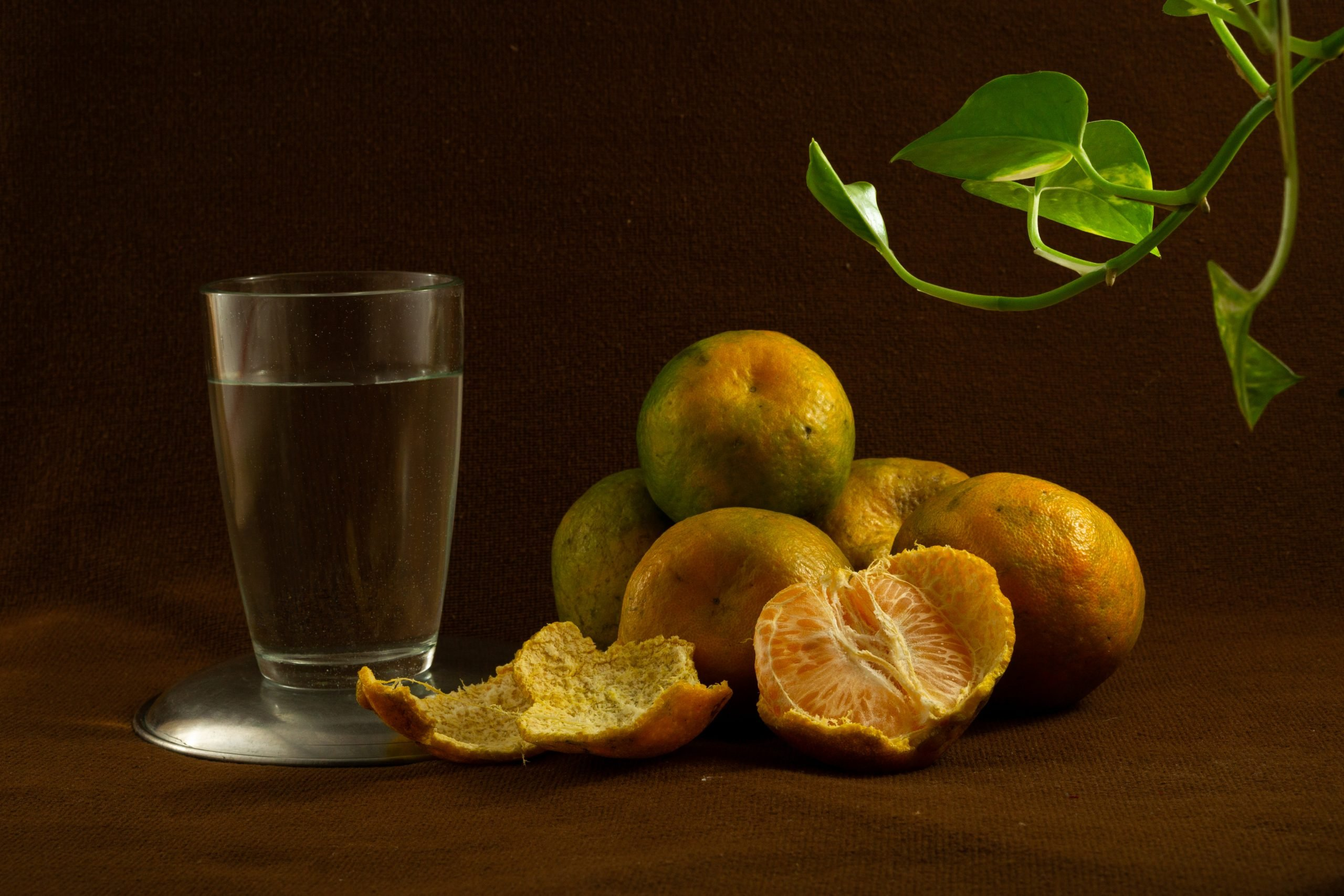 Fresh oranges and a glass of water
