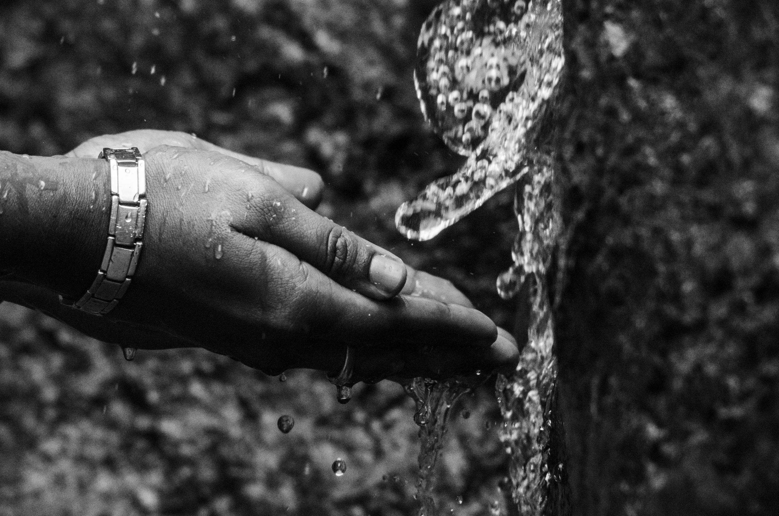 Hands toward a waterfall
