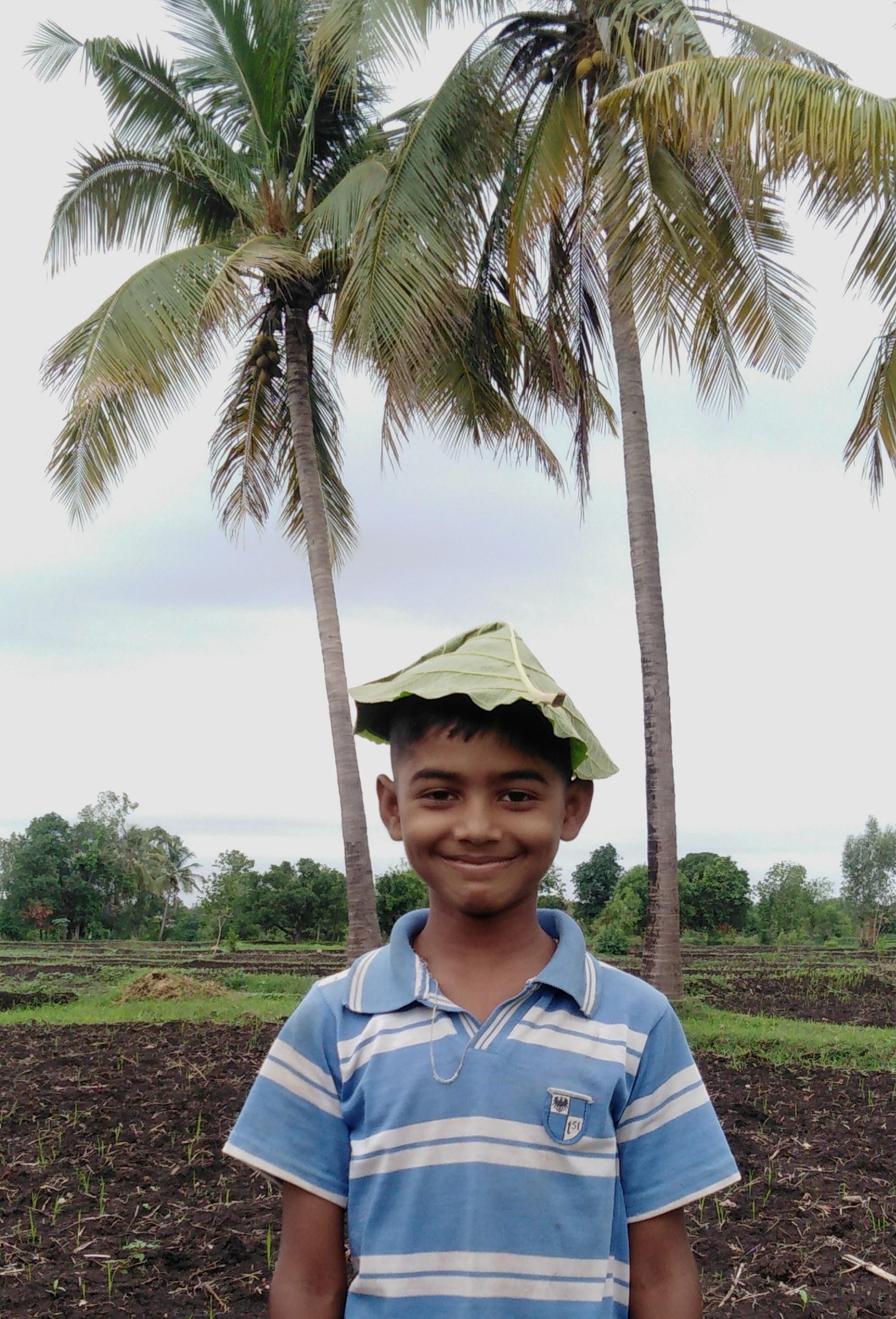 Happy kid with banana leaf on head