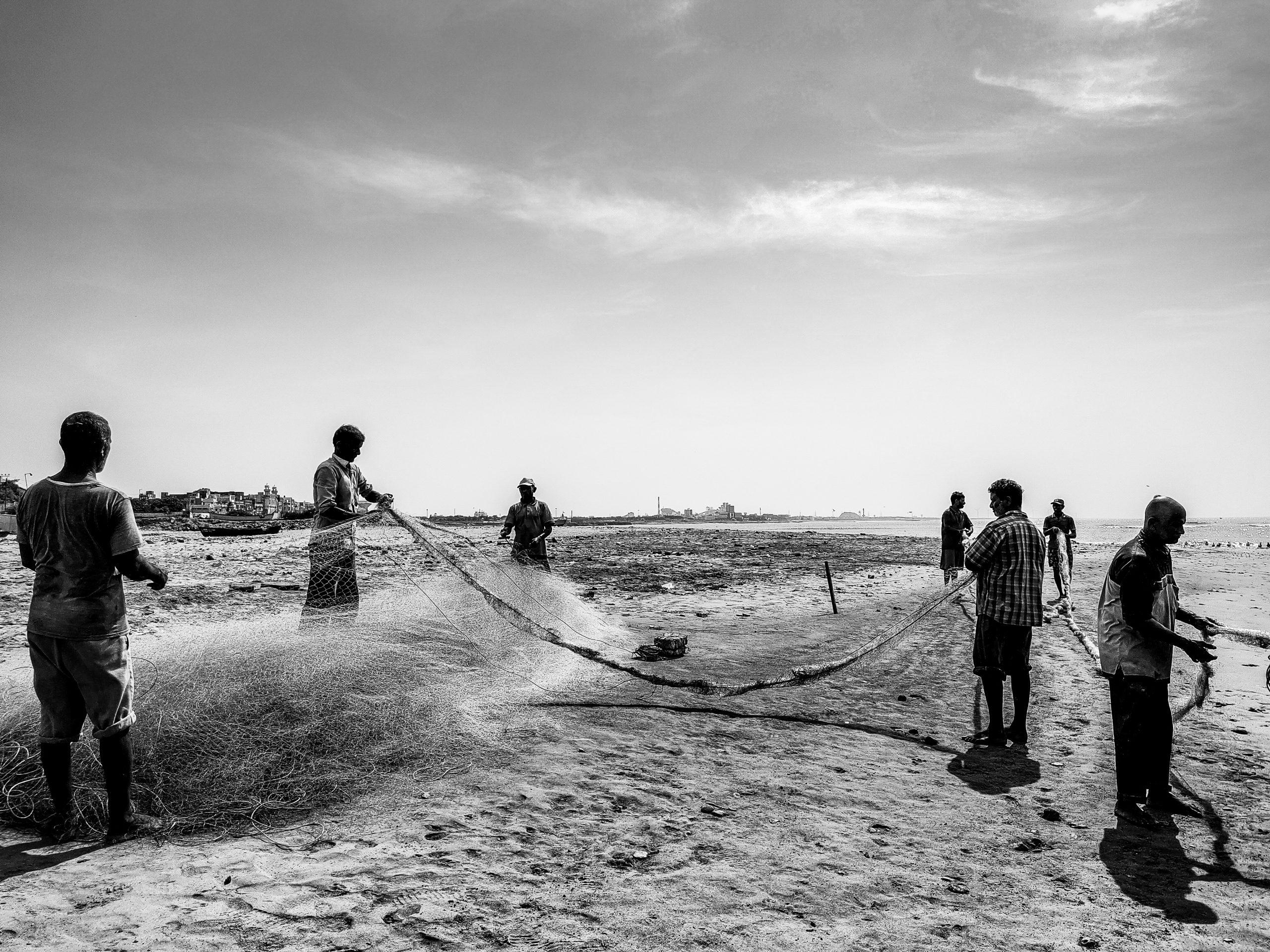 Fishermen with fishing net on a beach