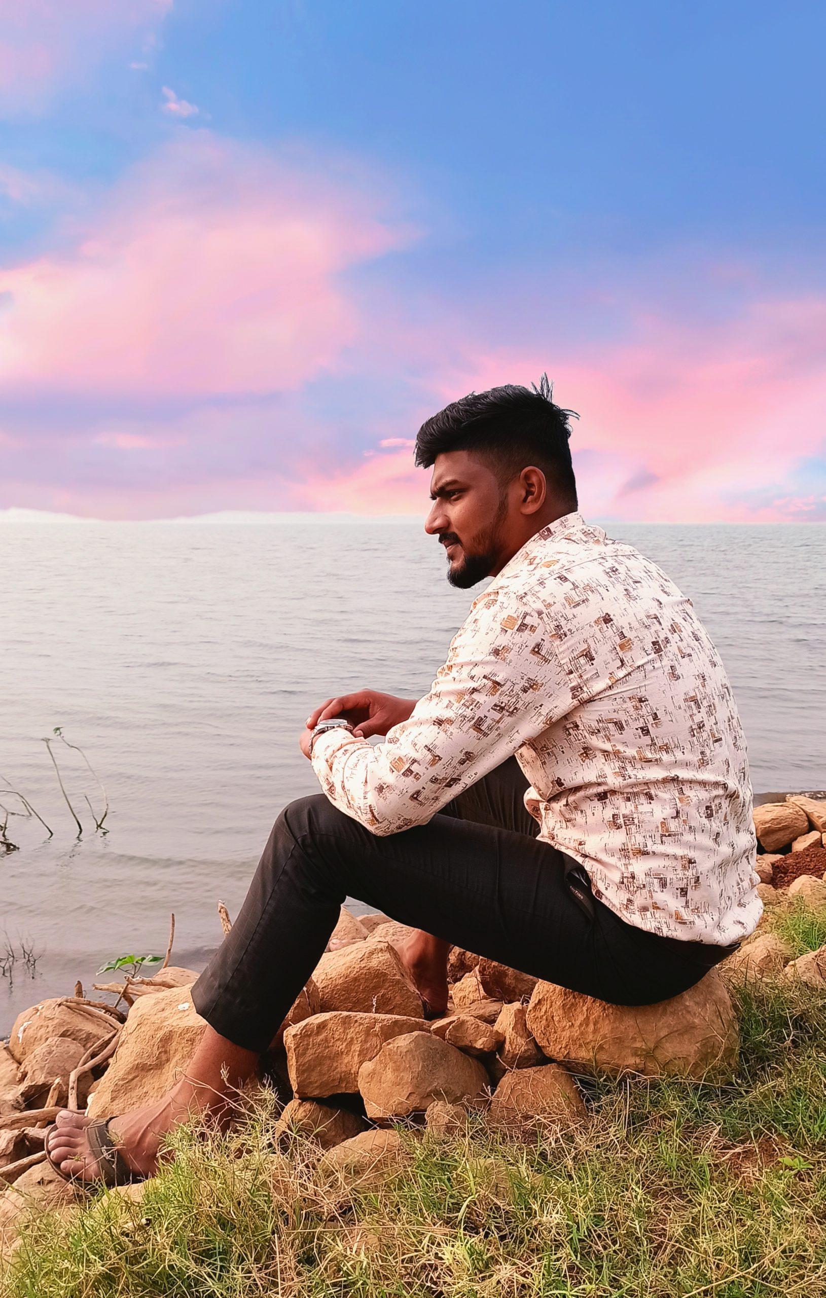 Man sitting on rock beach