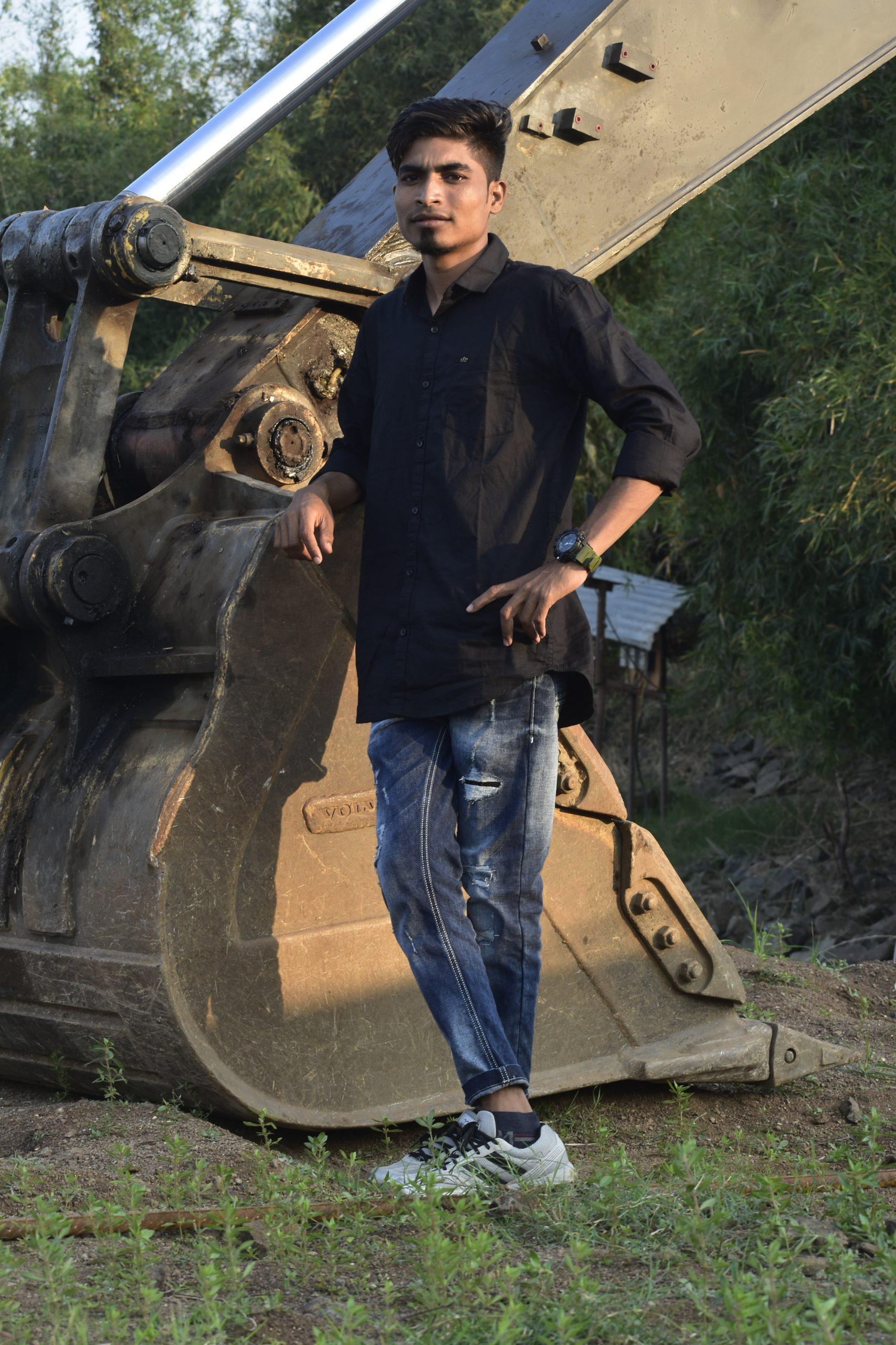 Boy posing in front of JCB
