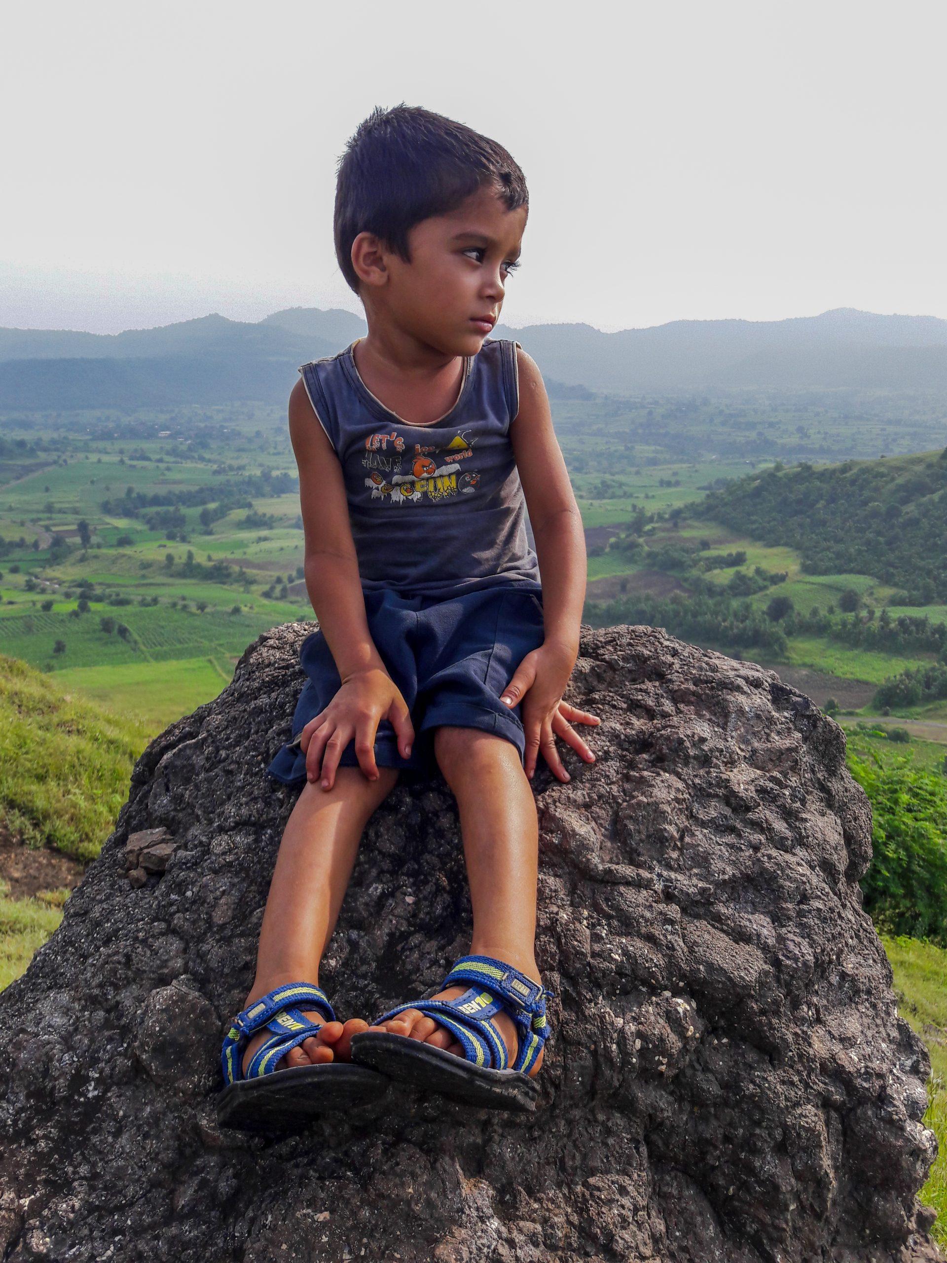 Kid sitting on rock