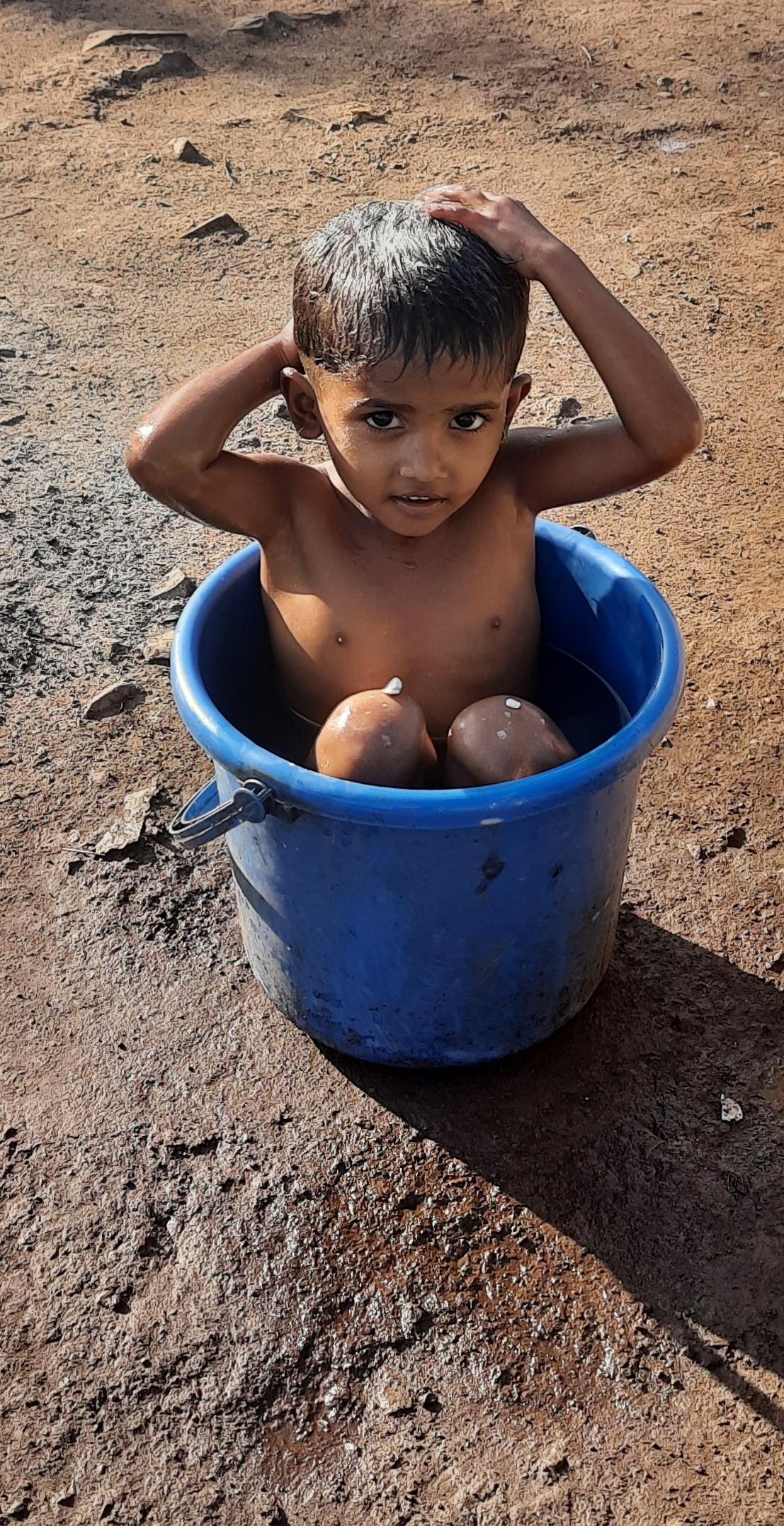 Kid bathing in the the bucket