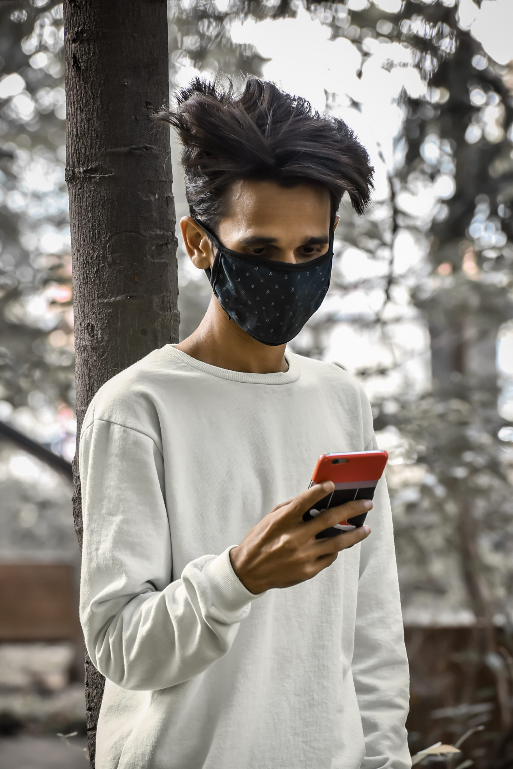 Boy using phone while wearing mask