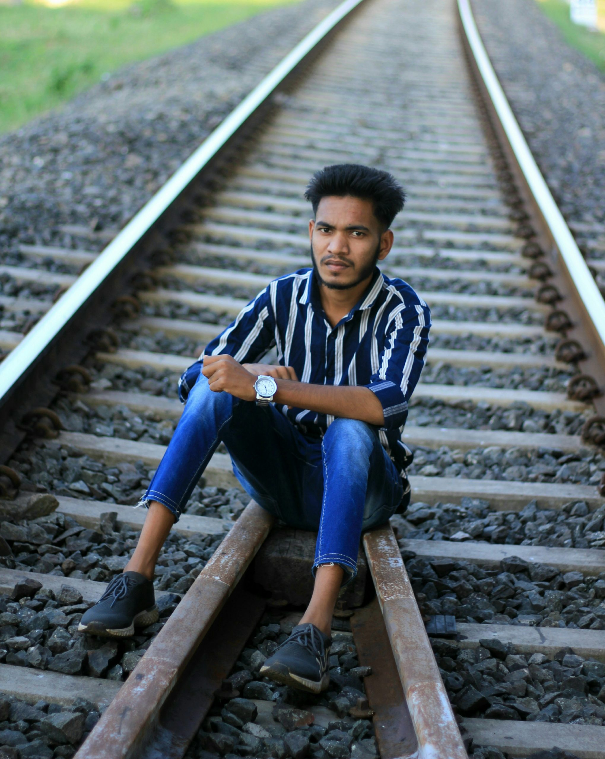 boy sitting on a rail track