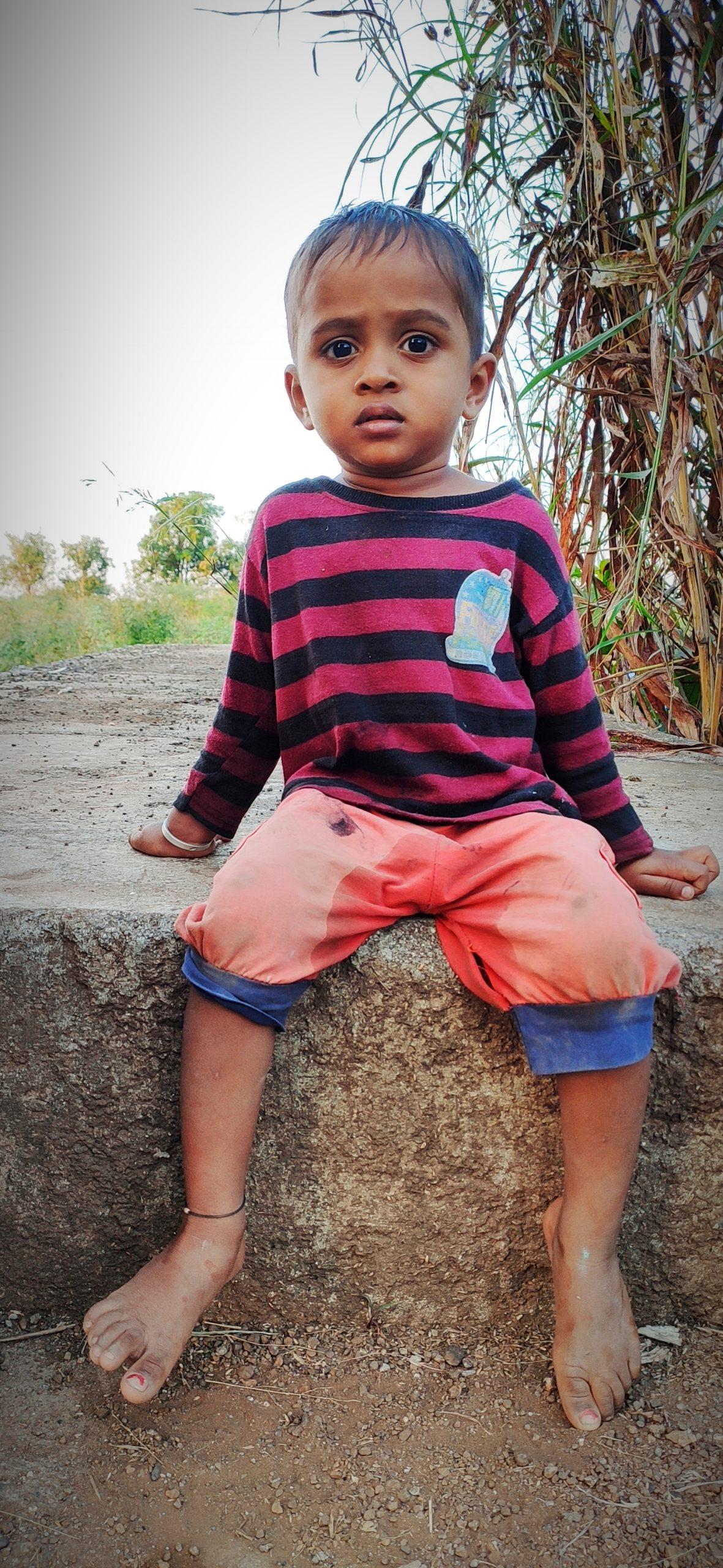 Little boy sitting on rock