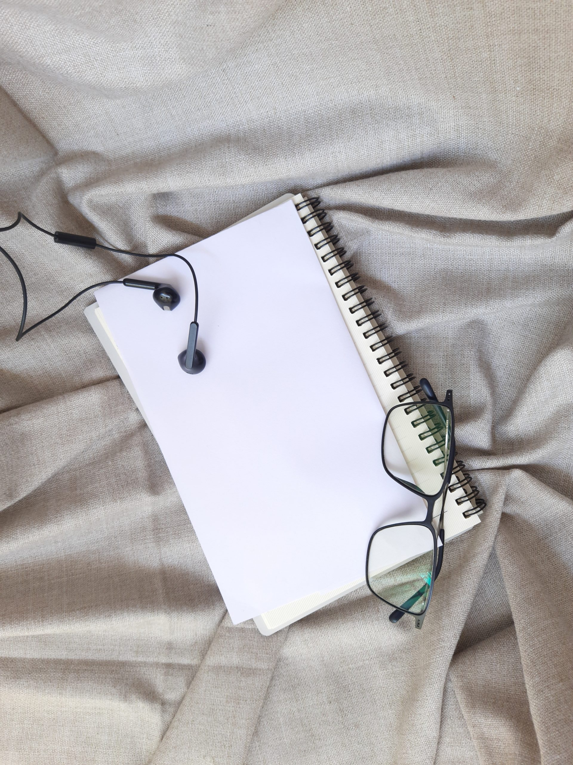 Diary and earphone on bed