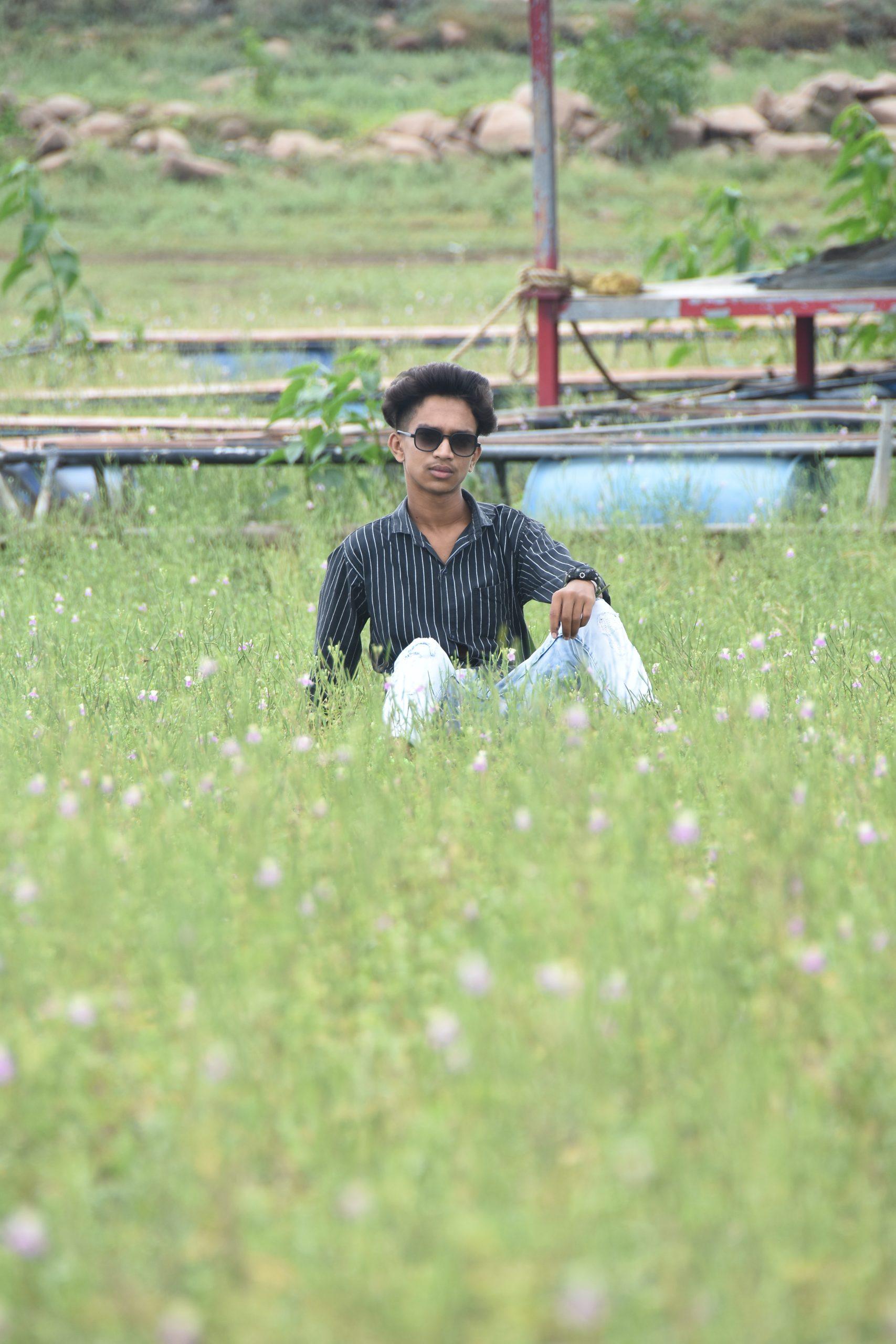 A boy sitting on grass