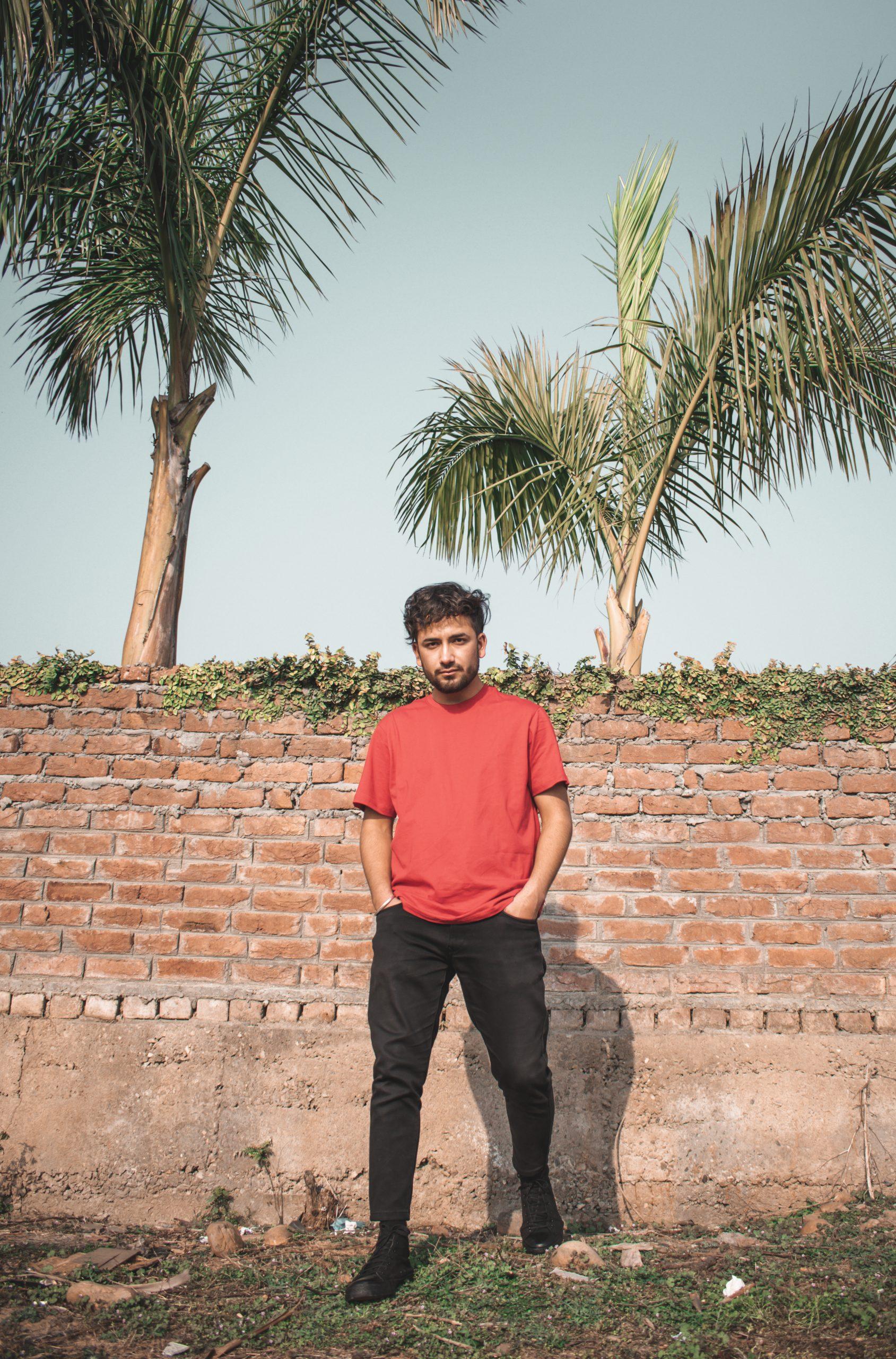A boy posing against the wall