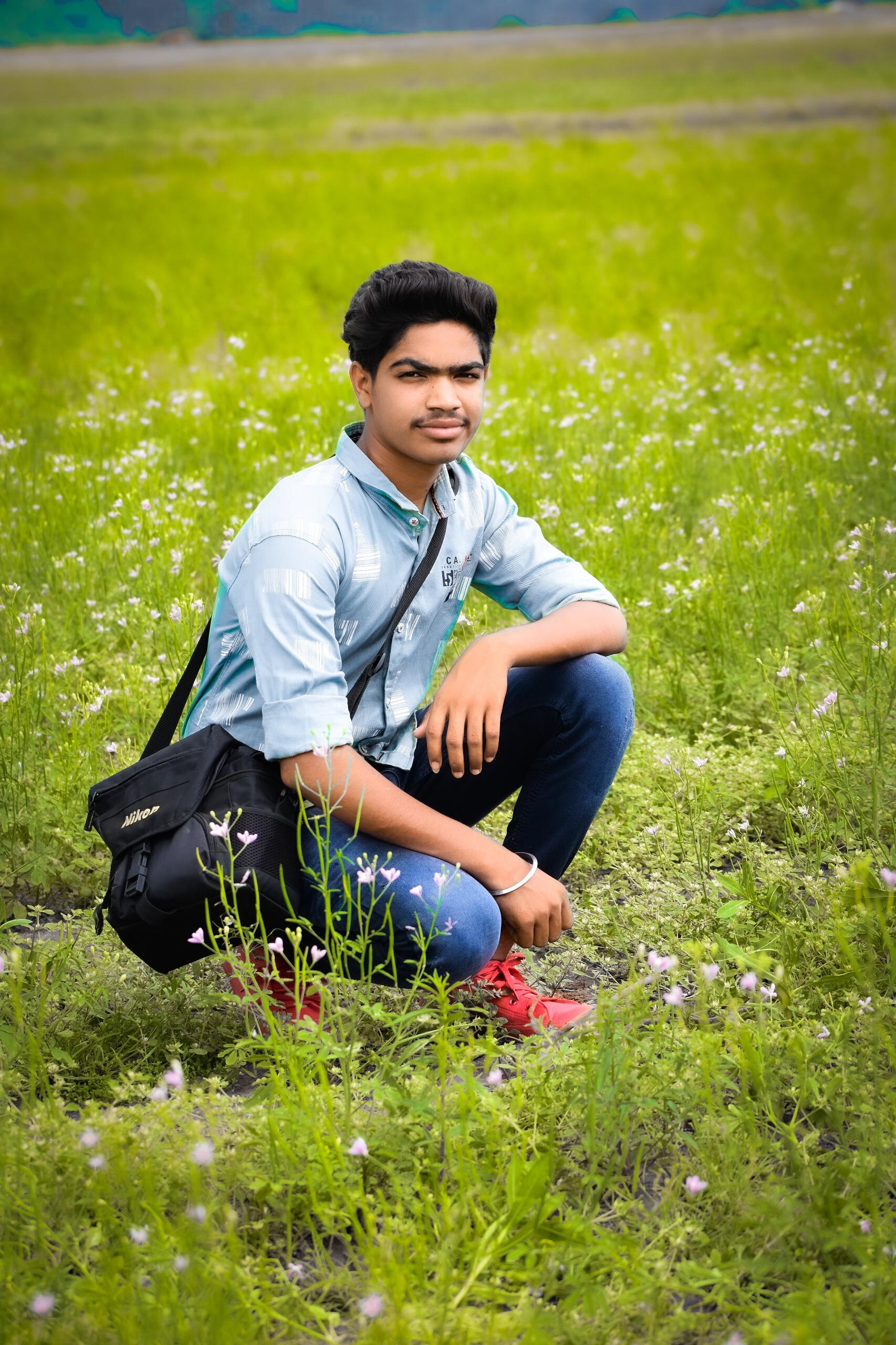 A boy sitting in grass
