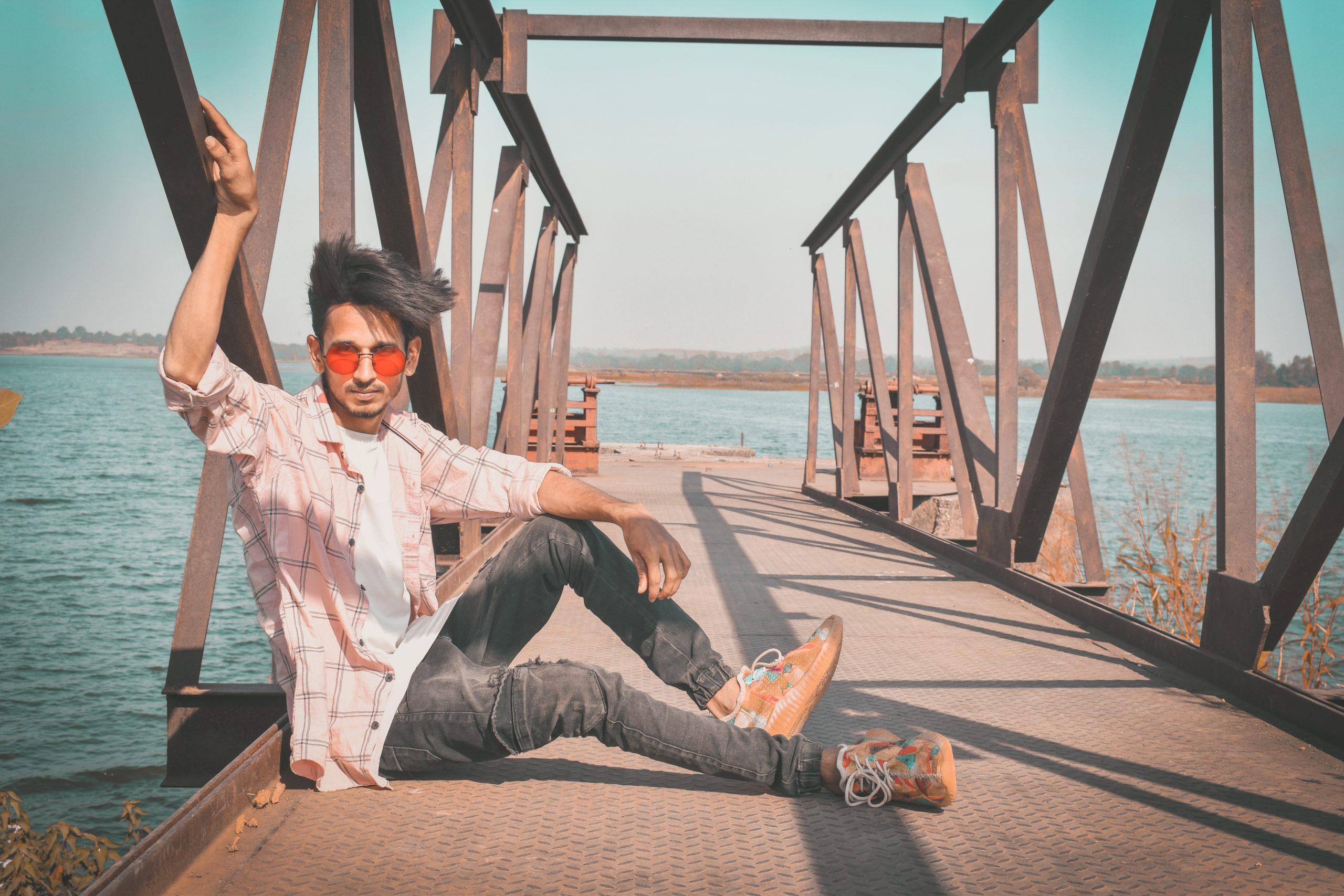 A boy sitting on a bridge