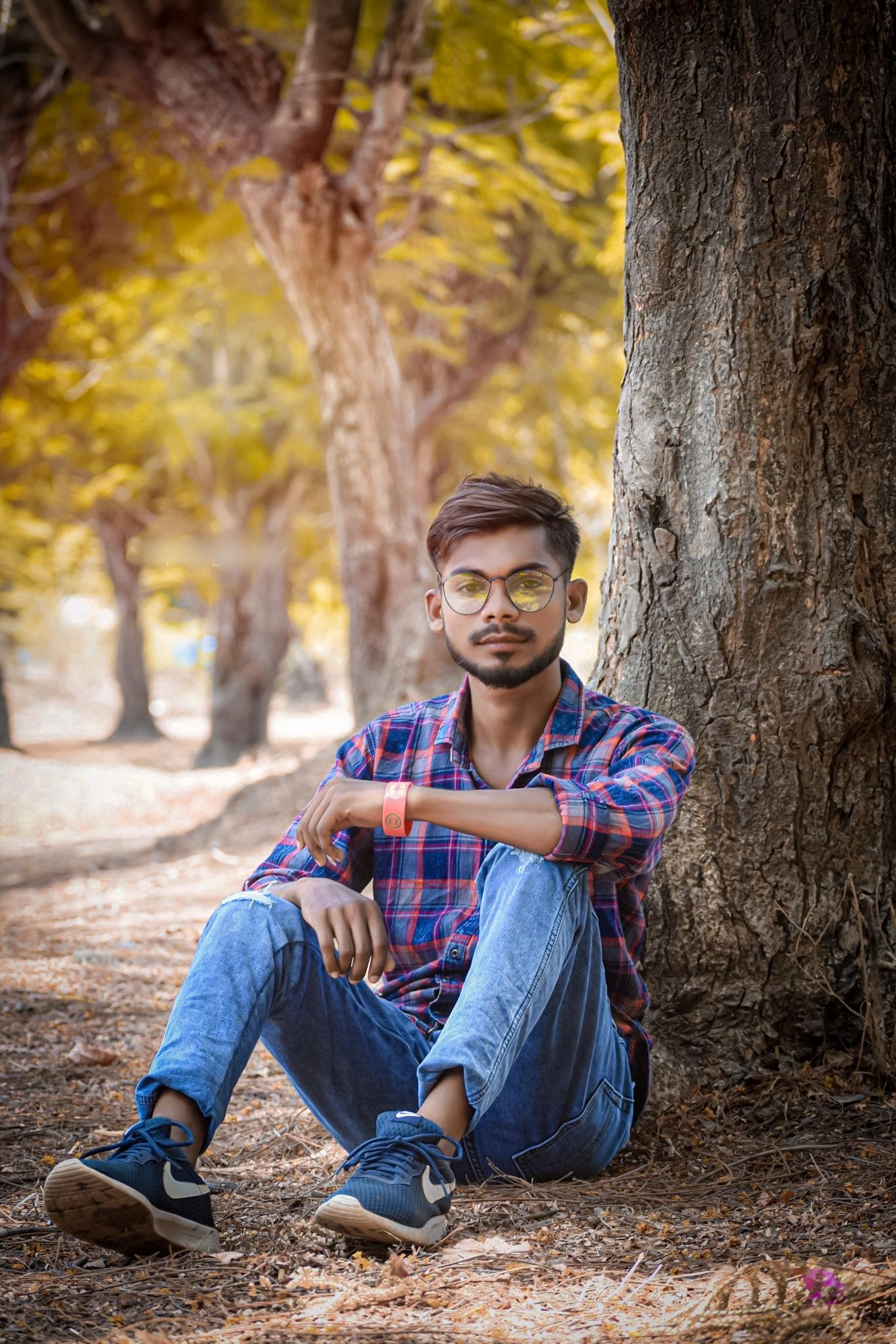 A boy sitting under a tree